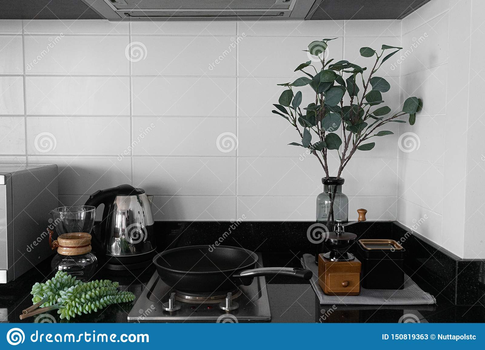 Cozy pantry corner / kitchen in scandinavian style white brick tile decoration and artificial plant in gray glass vase with hand c