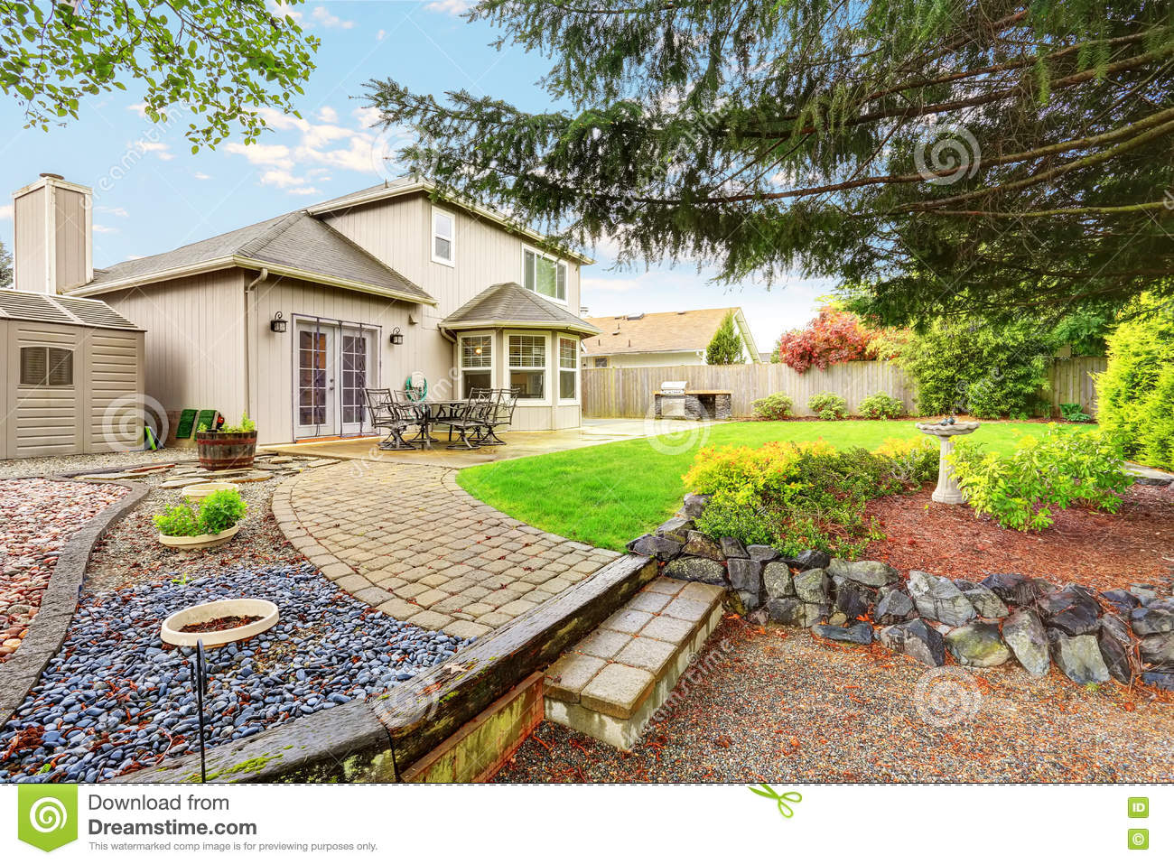 Cozy Patio Area With Concrete Floor And Table Set. Spacious Backyard Garden  With Nice Landscape Design.