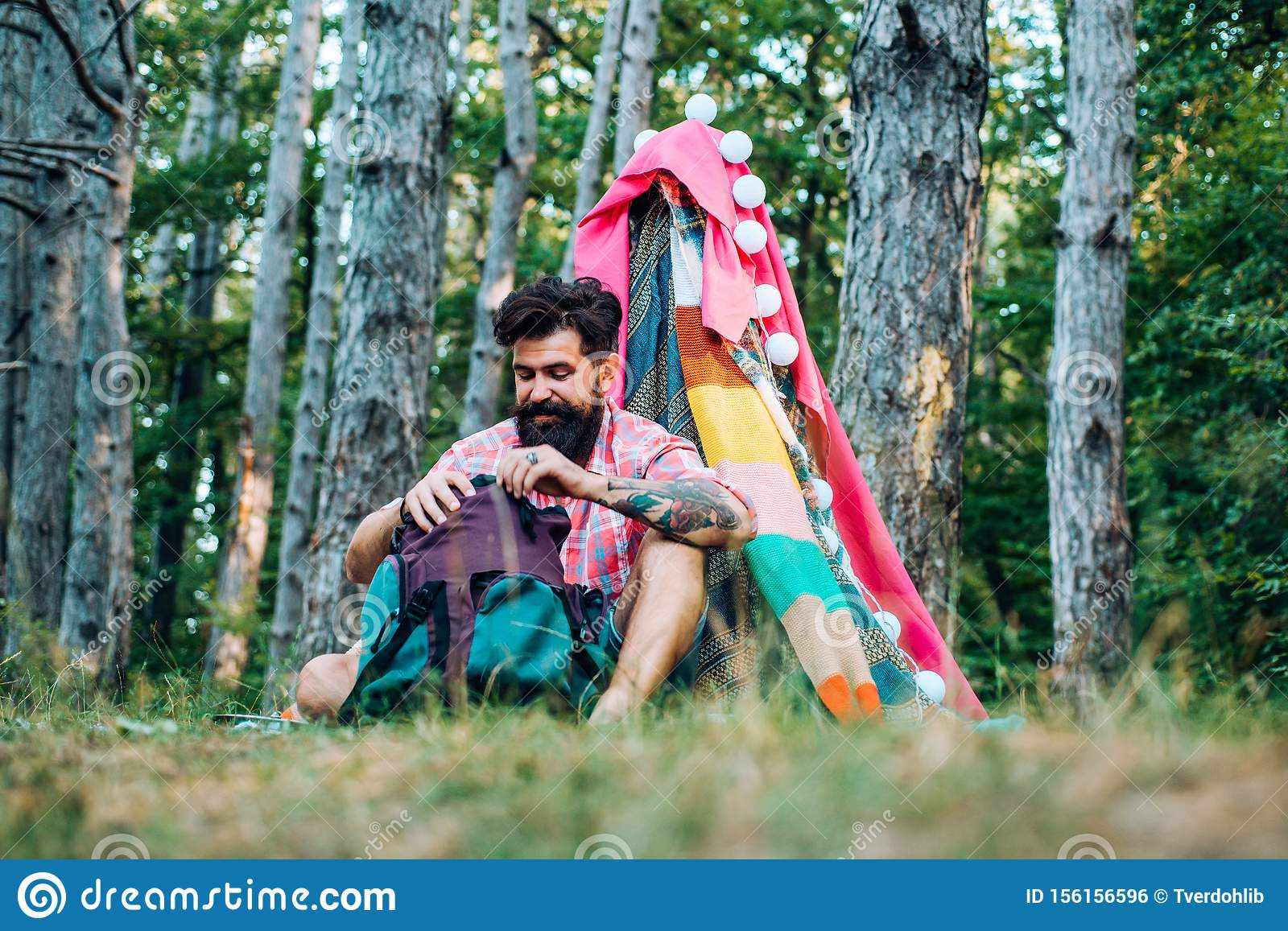 Cozy play tent for man in forest park. Hiking and outdoor recreation concept with flat camping travel. Handsome bearded