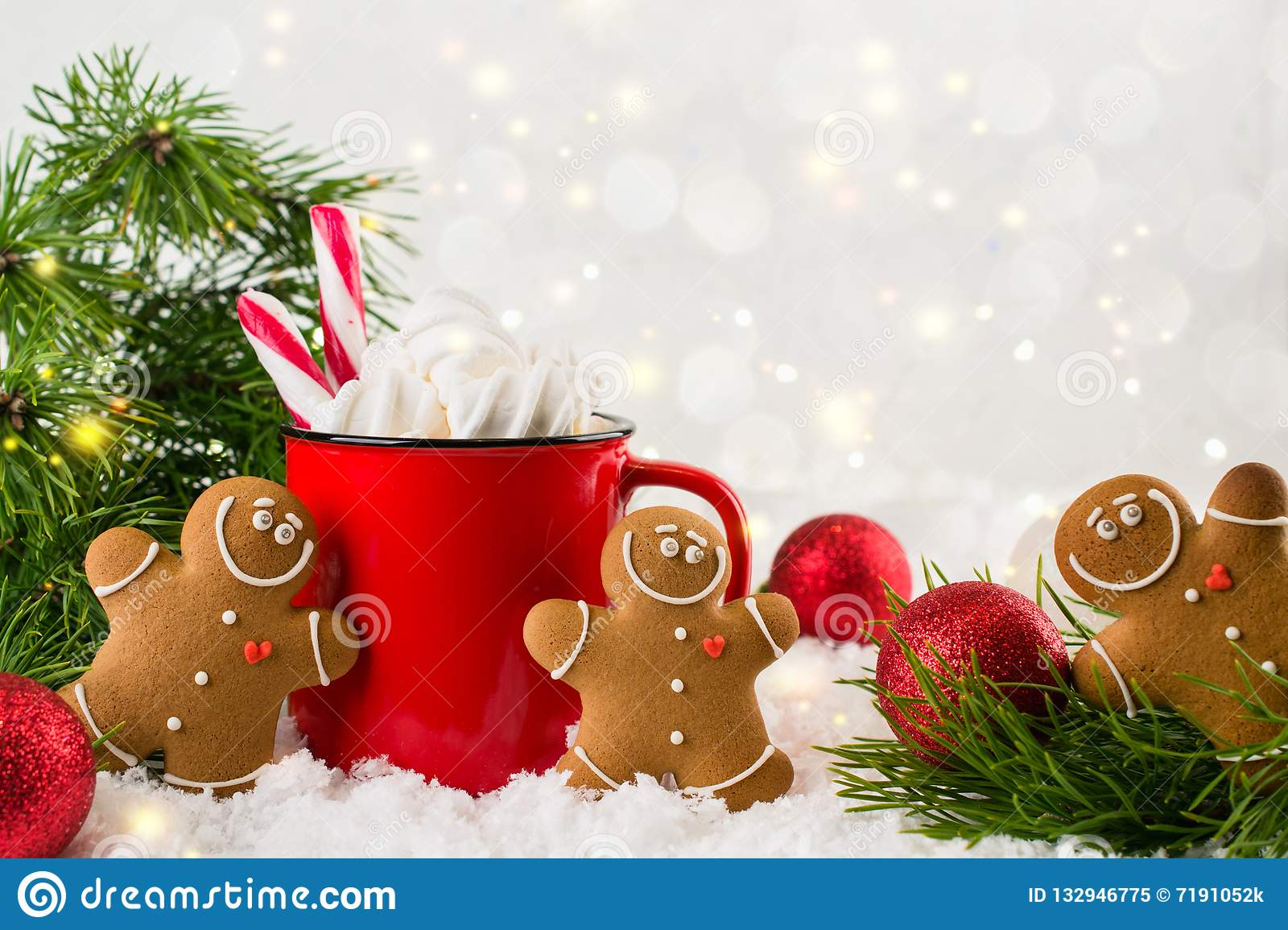 Cozy winter composition with a red cup of hot chocolate with marshmallows gingerbread man cookies on a festive background