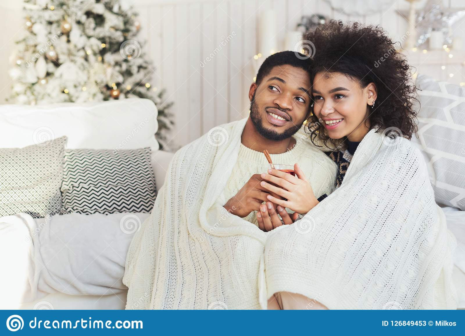 Couple relaxing with glass of warm wine on winter evening
