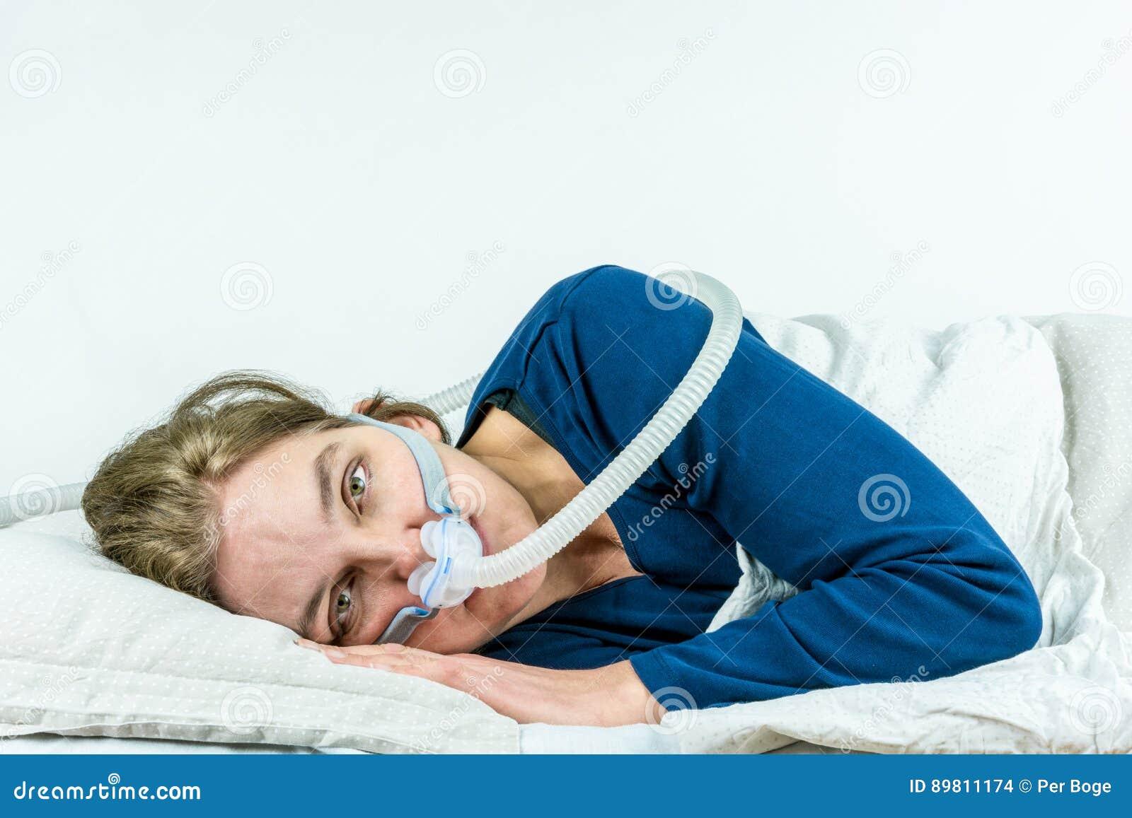 CPAP behandling för sömnapnea Kvinnan som lägger på hennes sida med ögon, öppnar