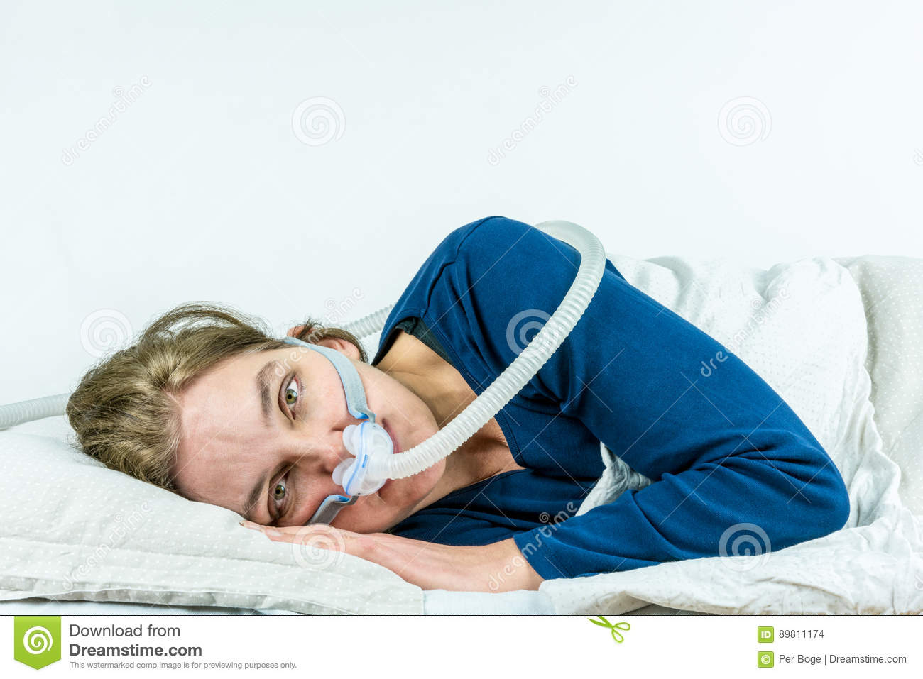 CPAP, sleep apnea treatment.Woman laying on her side with eyes open