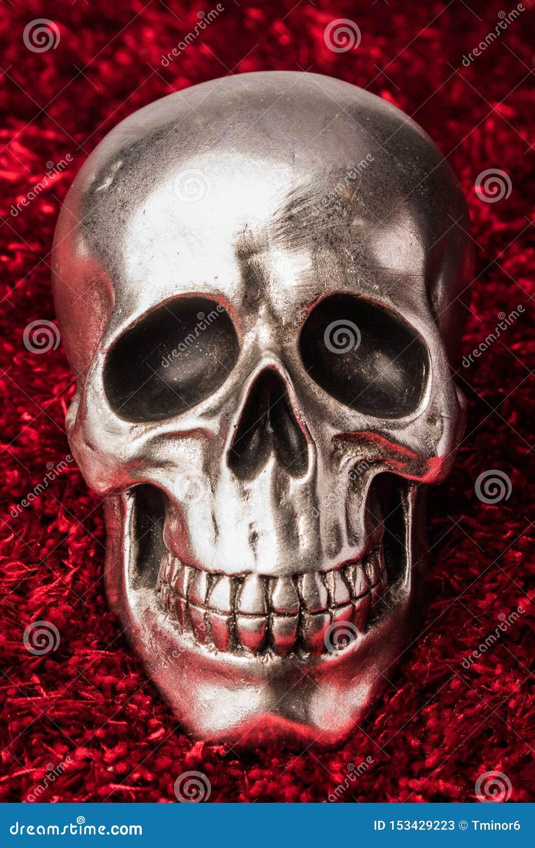 Crânio do metal em um fundo vermelho do tapete