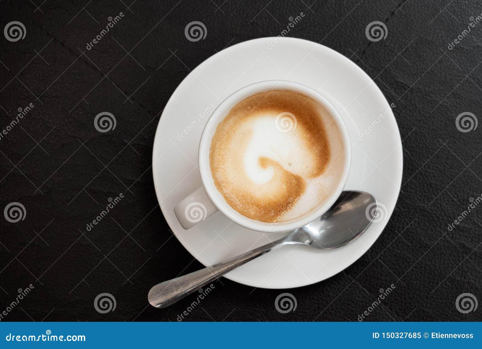 Crème d expresso dans la tasse en céramique blanche avec la cuillère en métal de soucoupe d isolement sur la surface en cuir noir