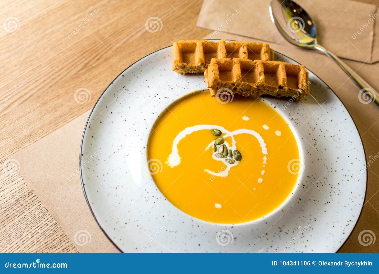 Crème de soupe à potiron et à carotte avec les gaufres belges sur le fond en bois clair Café, restaurant ou cuisine familiale E