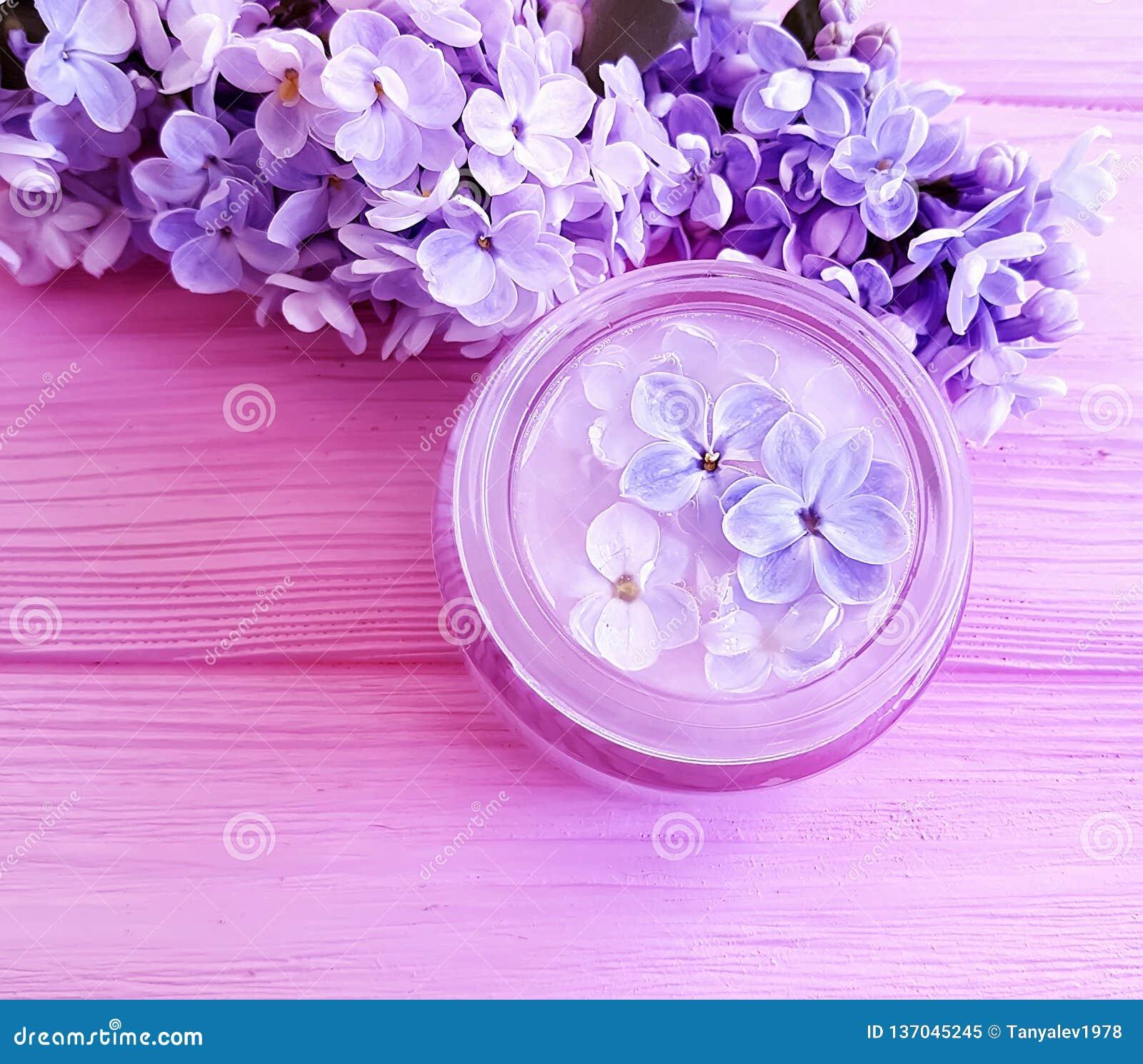 Crème naturelle cosmétique, beauté de ressort fraîche lilas de produit sur la lotion en bois d extrait de fond