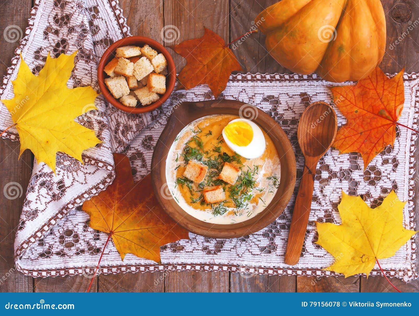 Crème-soupe à potiron décorée des feuilles, de l oeuf à la coque et du c d érable