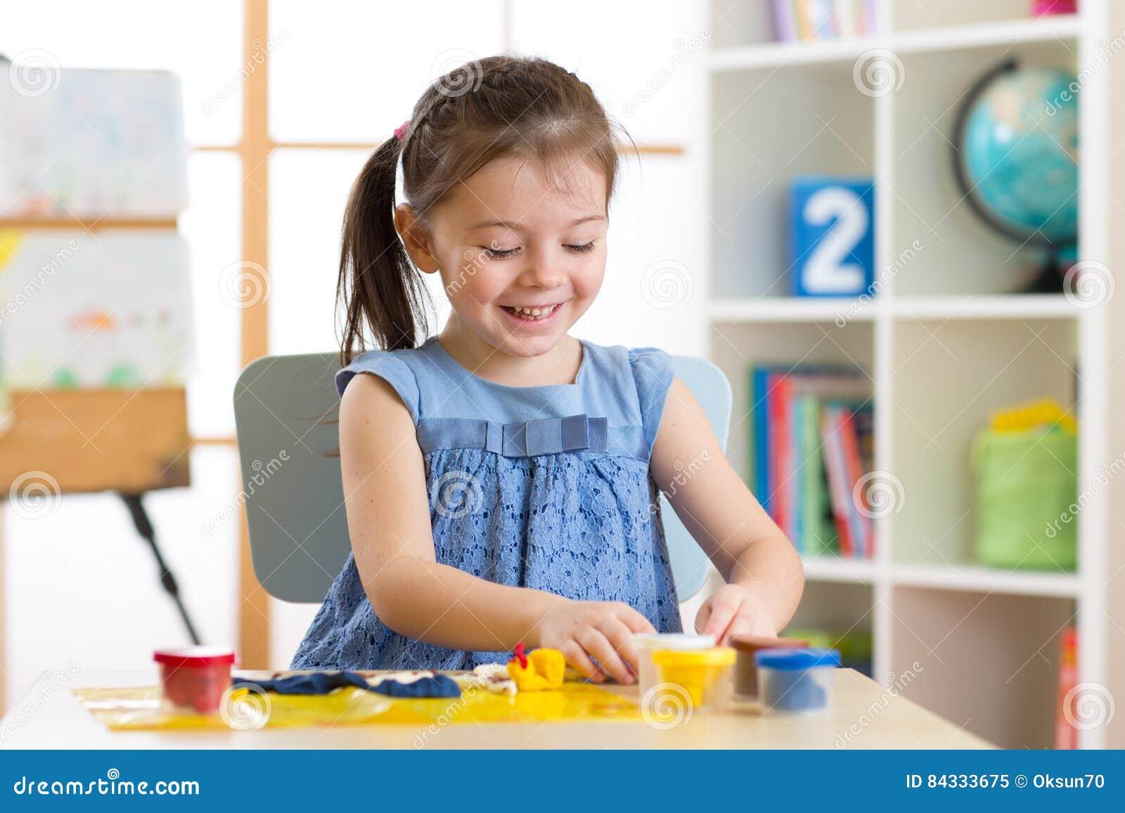 Créativité du ` s d enfants L enfant sculpte de l argile La petite fille mignonne moule de la pâte à modeler sur la table