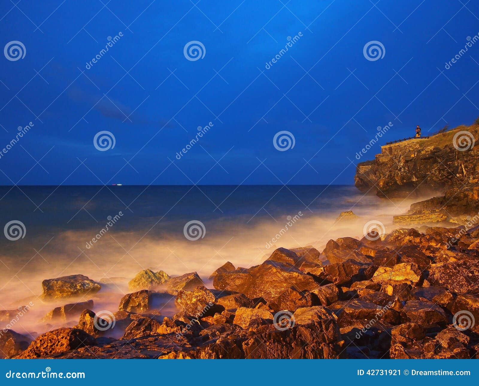 Crépuscule aux roches et aux vagues de bord de la mer