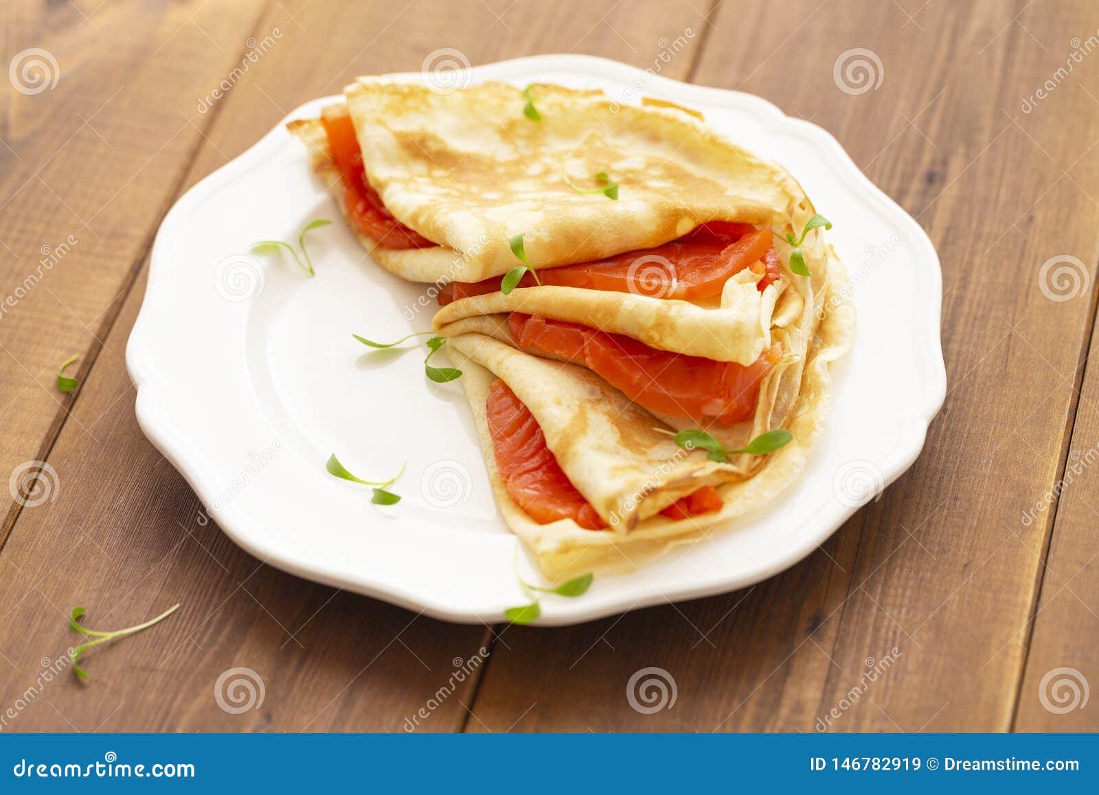 Cr?pe con il salmone affumicato su un piatto bianco Prima colazione deliziosa e sana