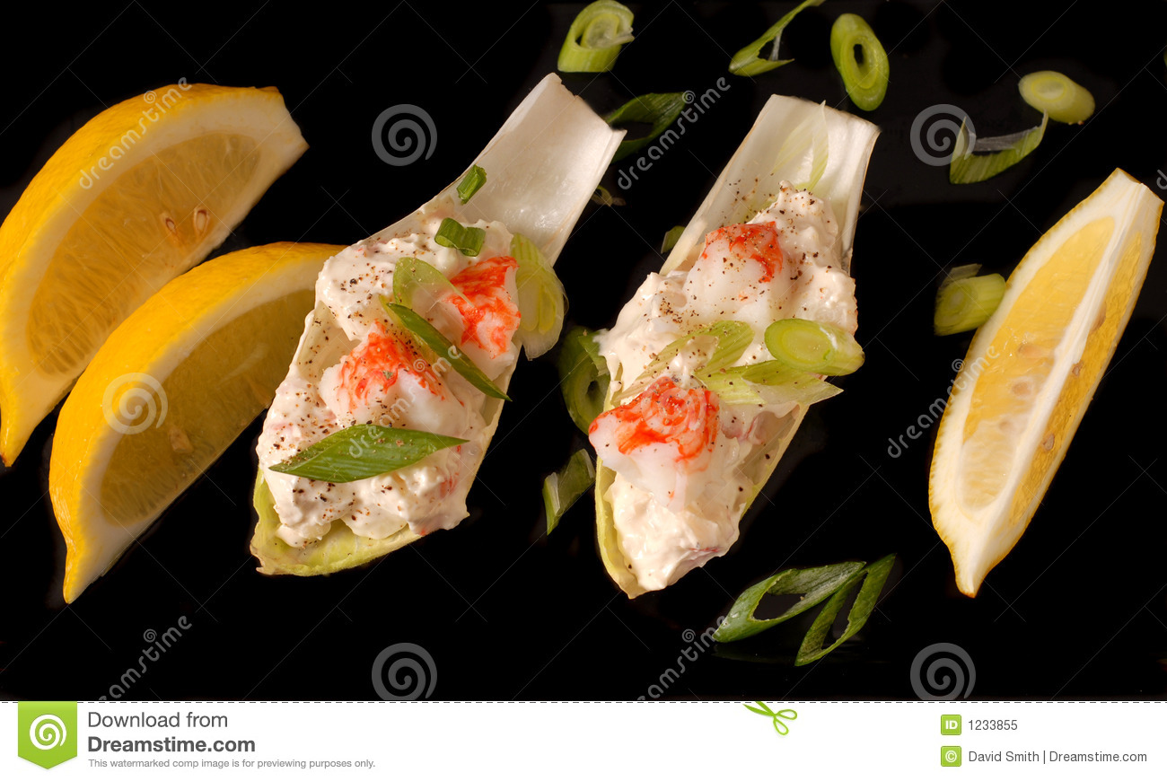 Crab salad on endive leaves with lemon and chopped scallions on black ...