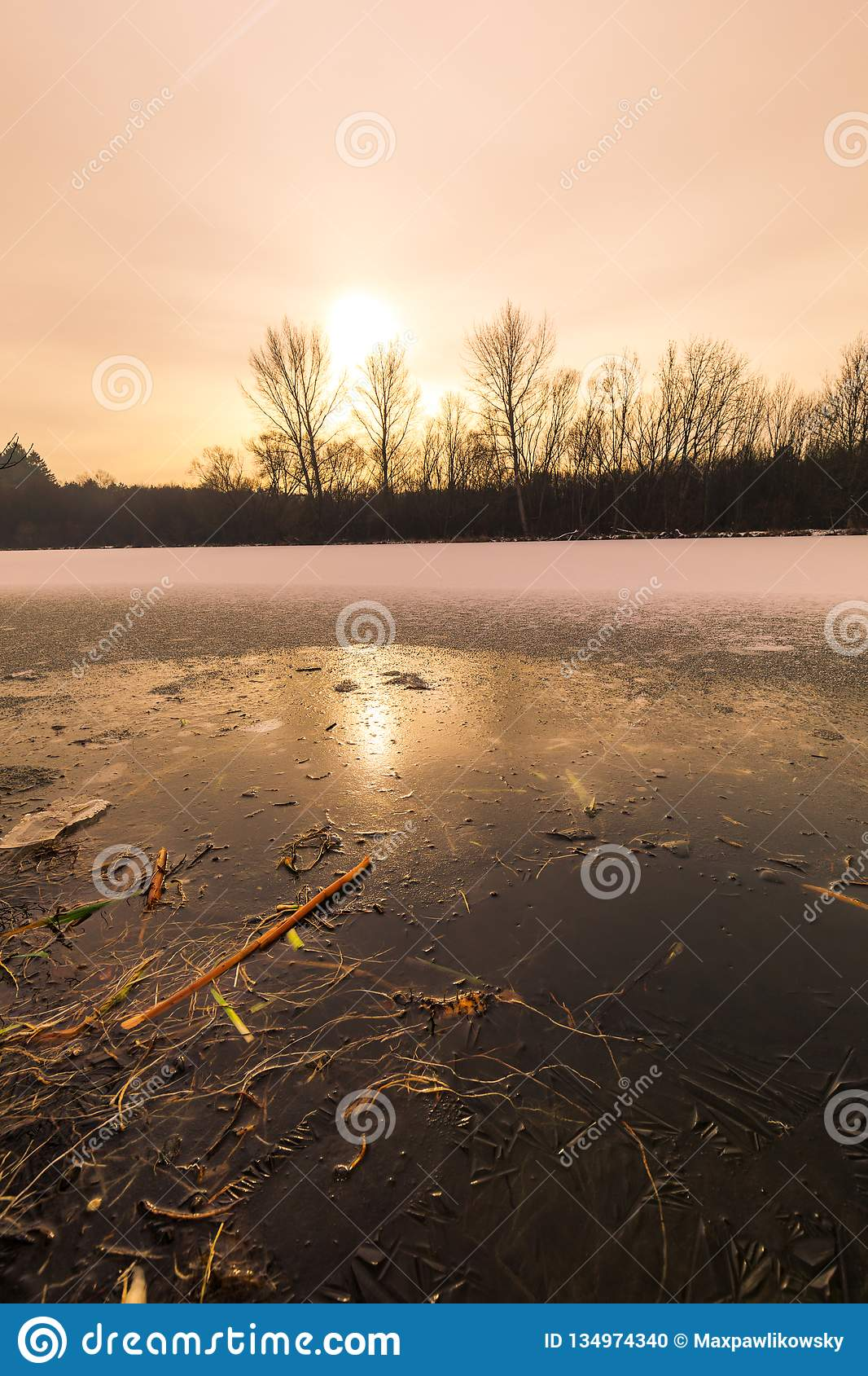 Cracks on the surface of the blue ice. Frozen lake in winter mountains landscape