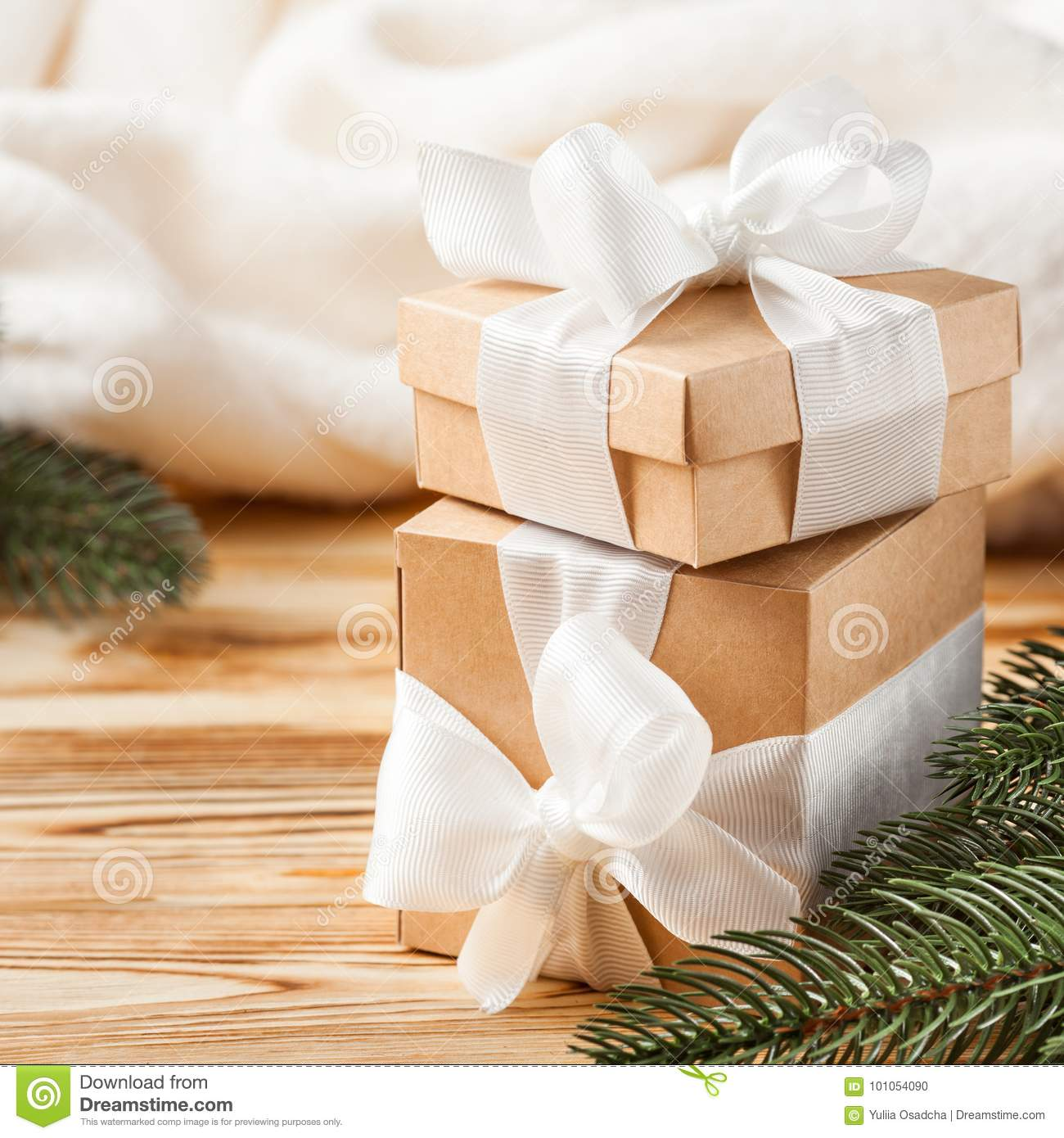 Craft gift boxes with white ribbon, bow, green Christmas tree, decorations, white plaid on wooden background. Xmas and New Year co