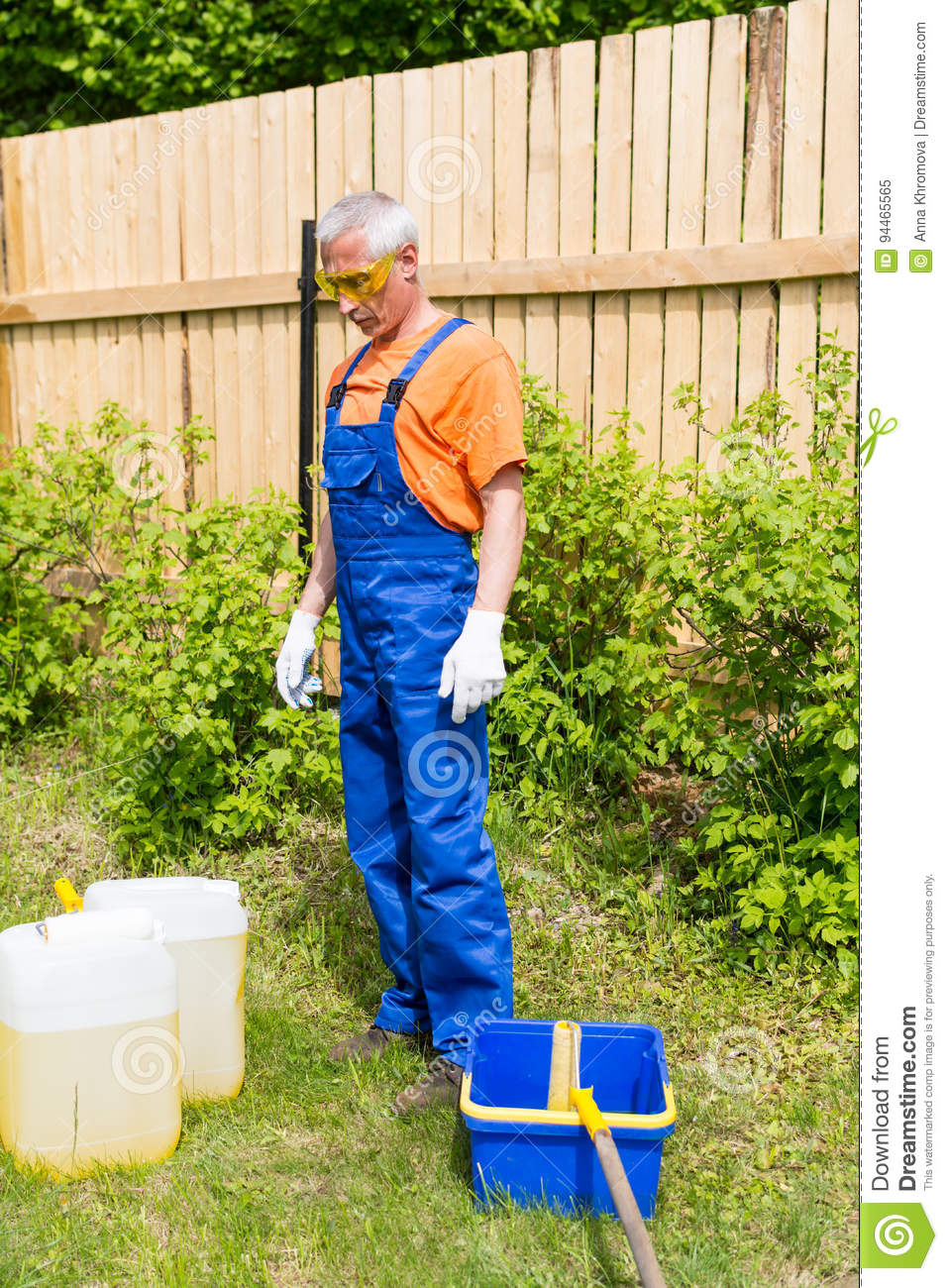 Craftsman In Blue And Orange Uniform Looking At Paint Cans And Bucket In The Garden Stock Image Image Of Equipment Baseball 94465565