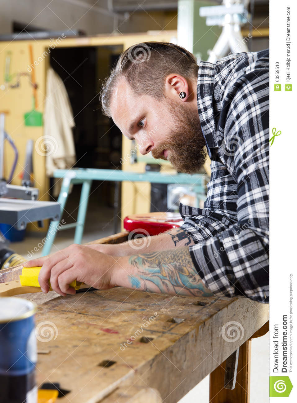 Craftsman sanding a guitar neck in wood at workshop stock for Working man tattoo