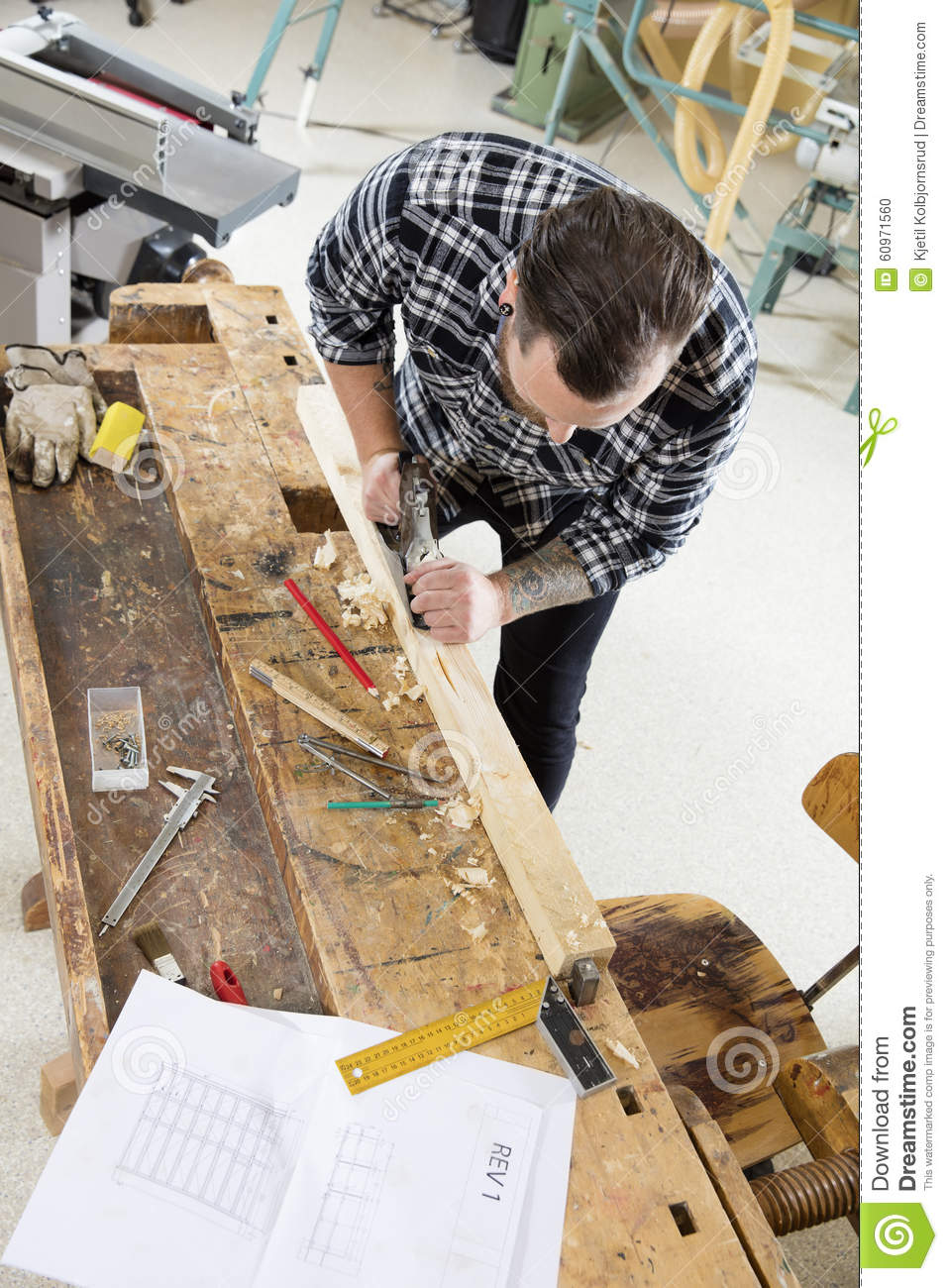 Craftsman work with plane on wood plank in workshop stock for Working man tattoo