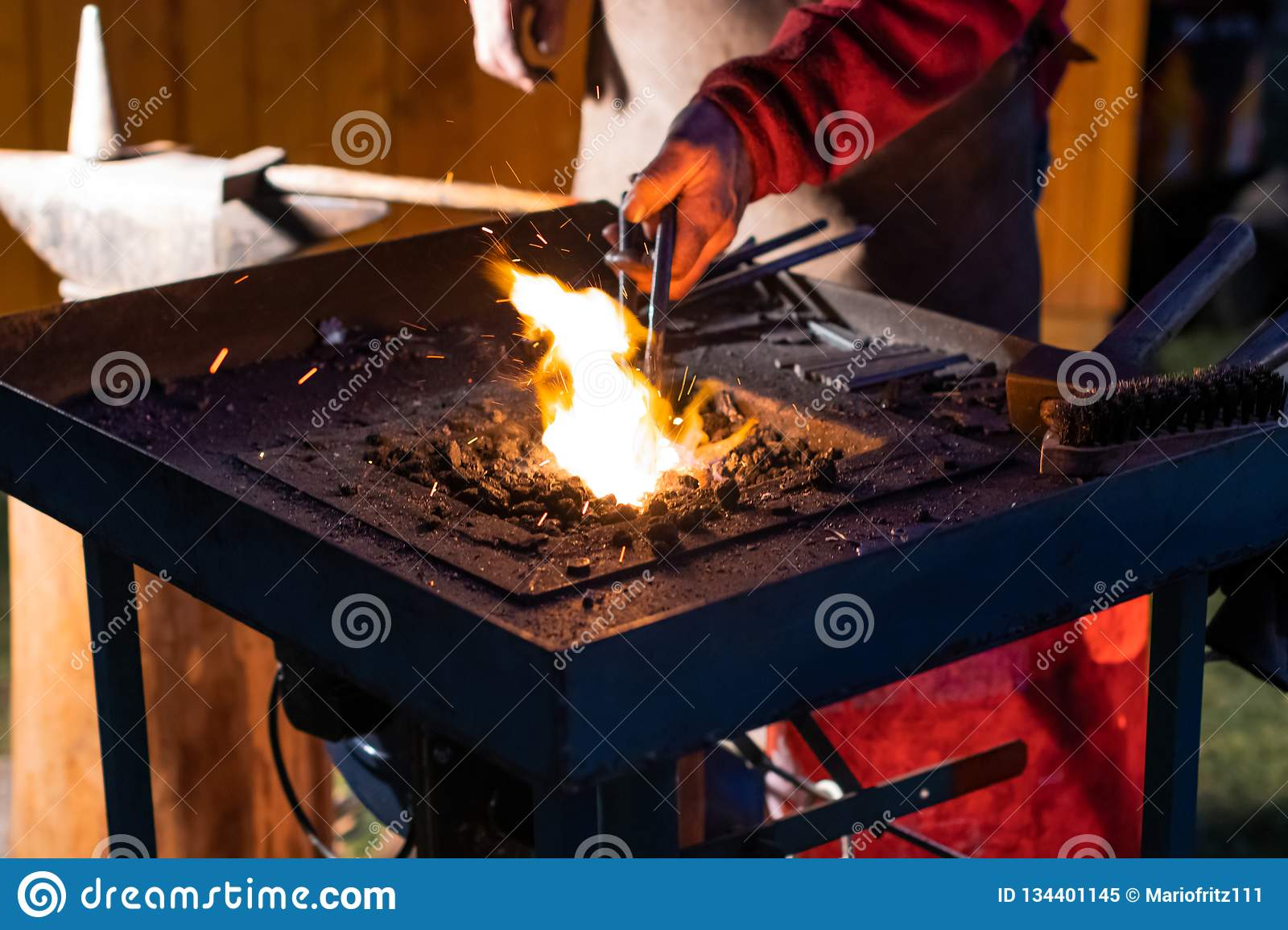 A Craftsman Working With Fire And A Hammer On A Glowing Iron