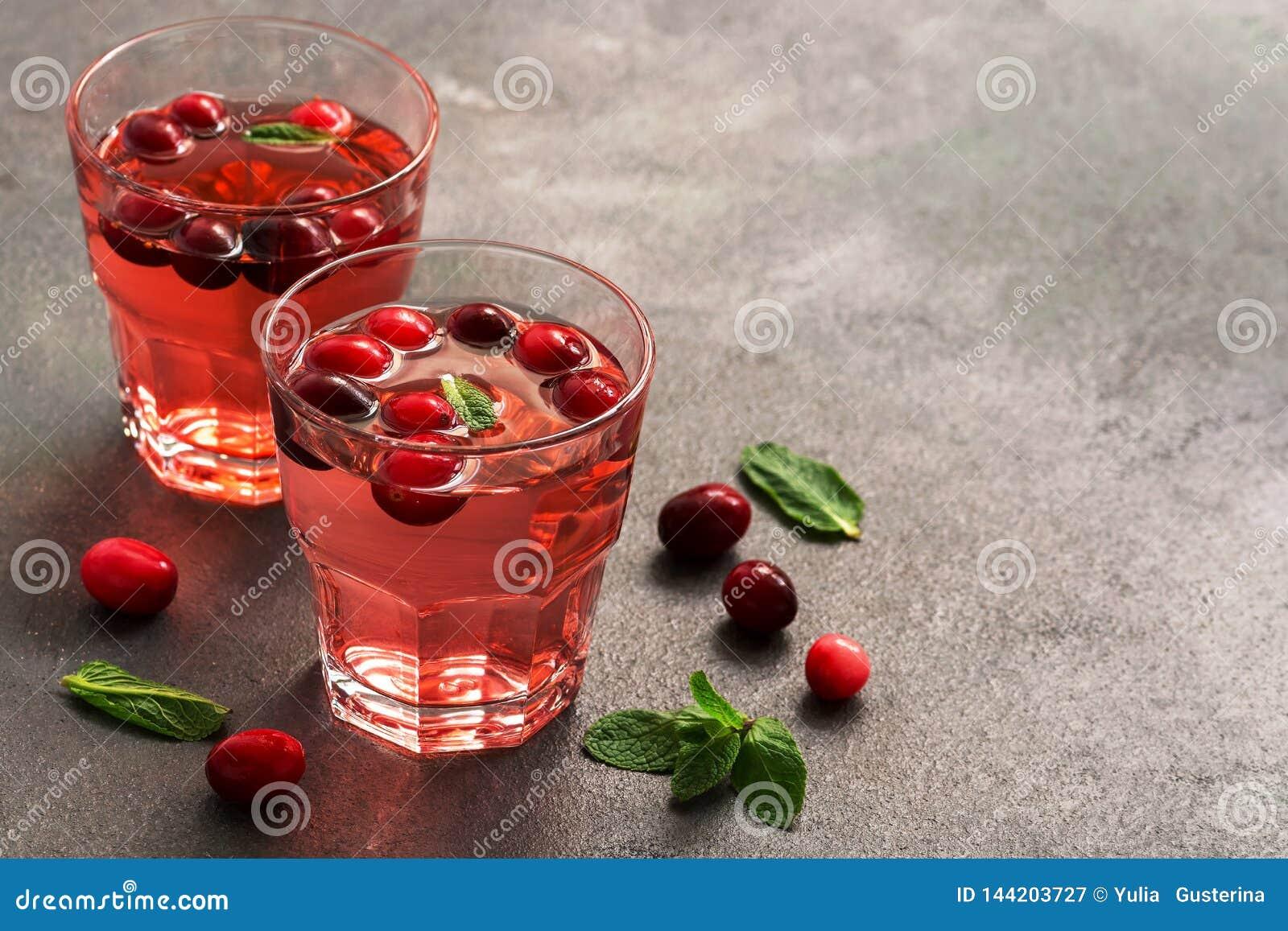Cranberry sok w szkłach z nowymi liśćmi na zmroku stole Selekcyjna ostrość, miejsce dla teksta