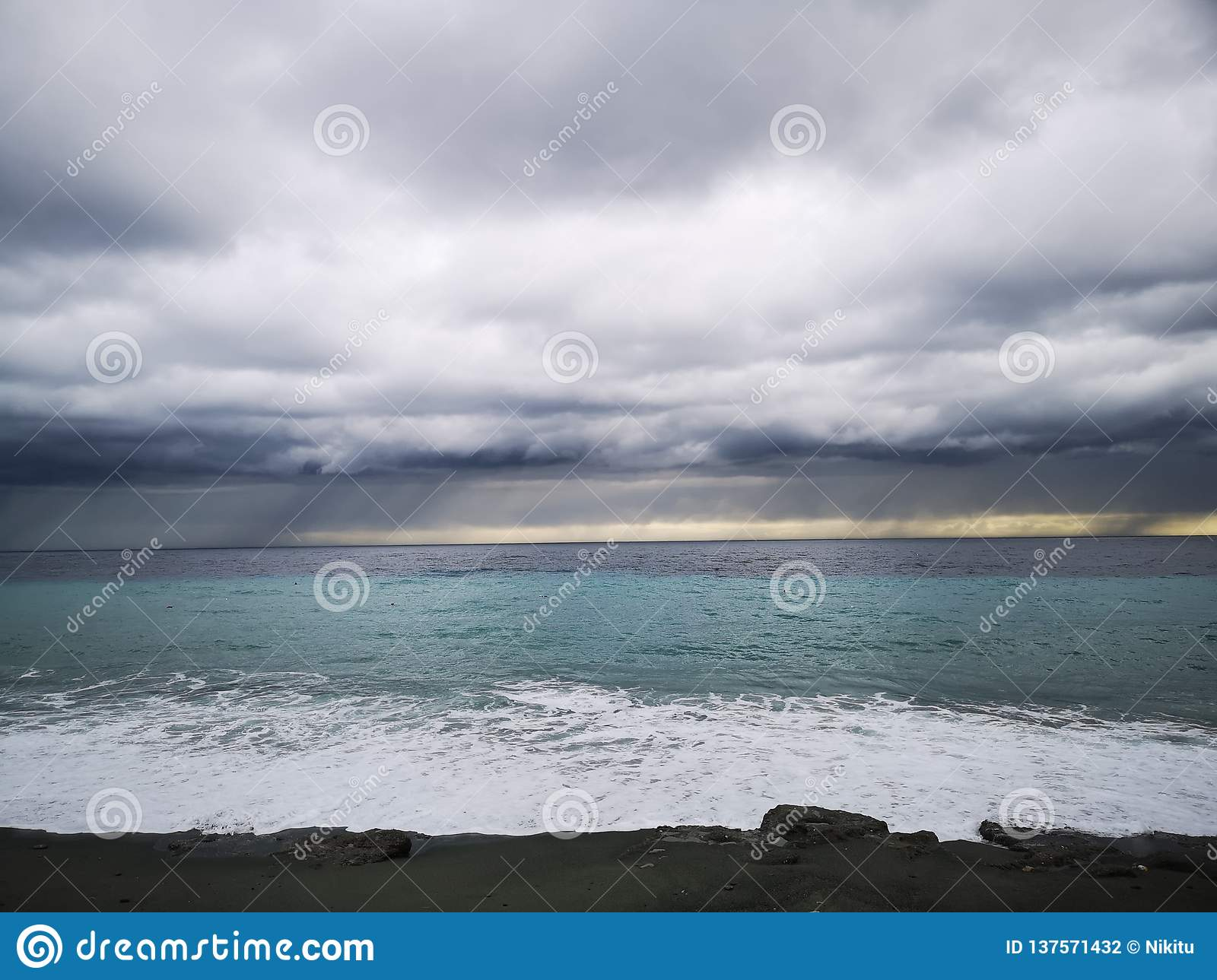 Crashing waves on beach with storm clouds