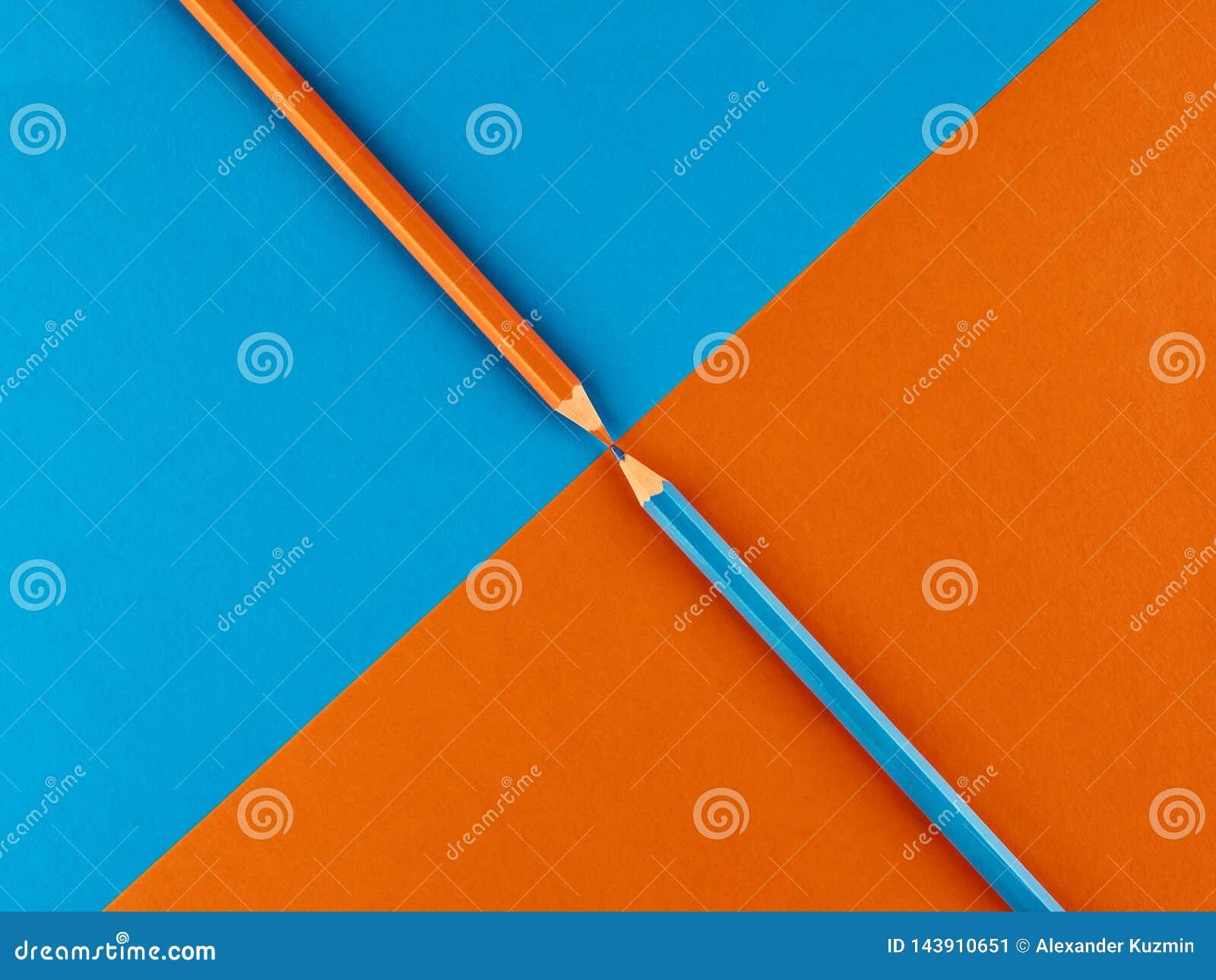 Crayon bleu et orange sur un fond contrastant