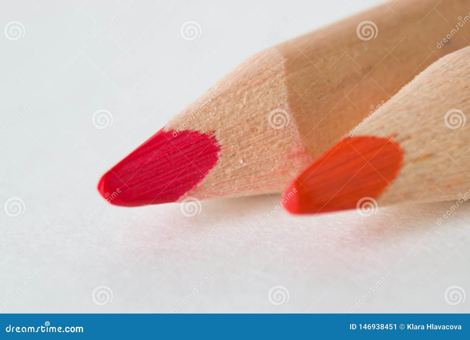 Crayons rouges et roses sur le fond blanc