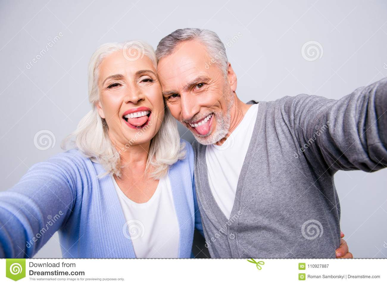 Crazy funky funny elderly couple are taking selfie using smartphone and showing tongues, isolated on grey background