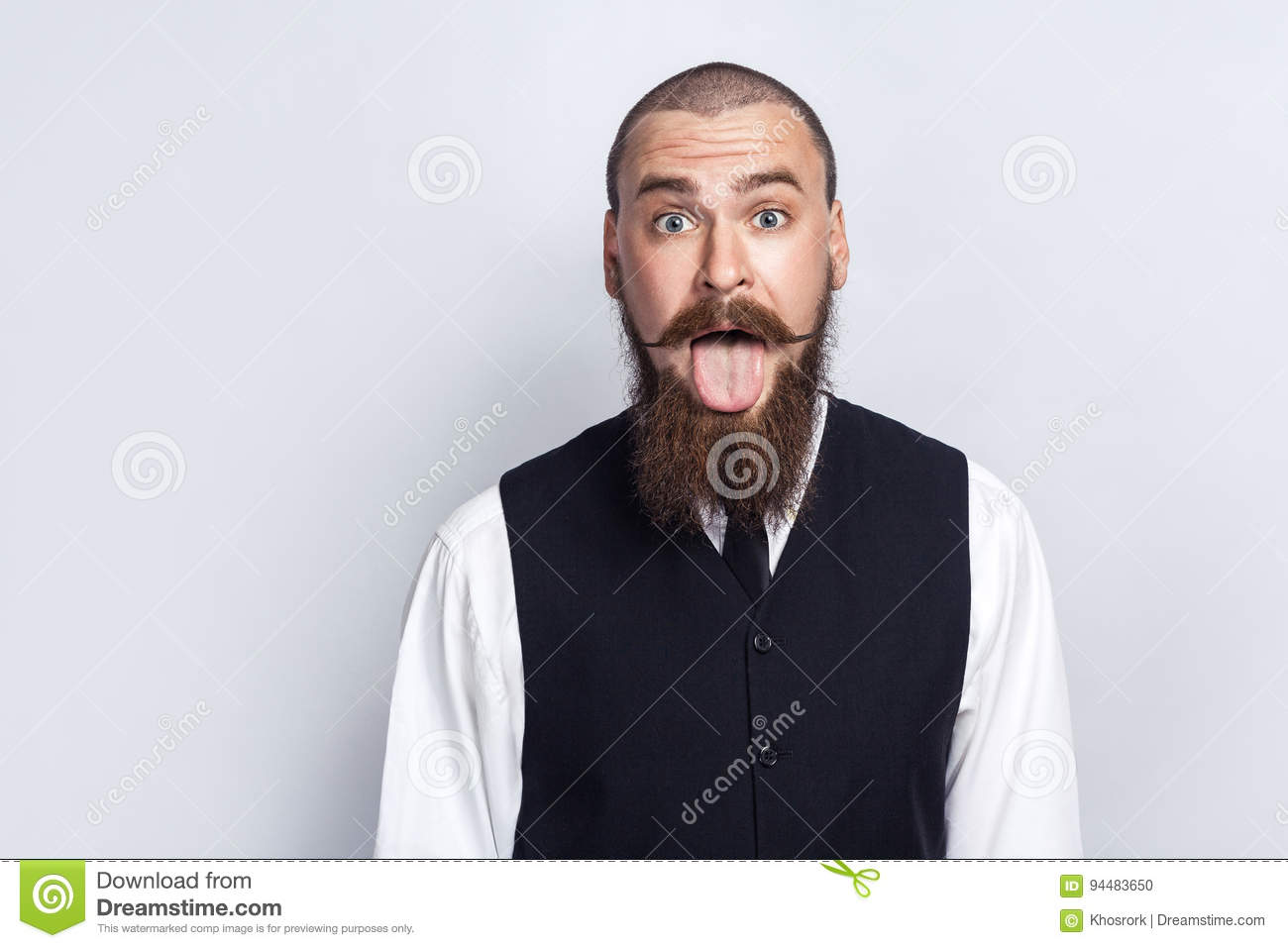 Crazy Funny face. Handsome businessman with beard and handlebar mustache looking at camera with tongue out.