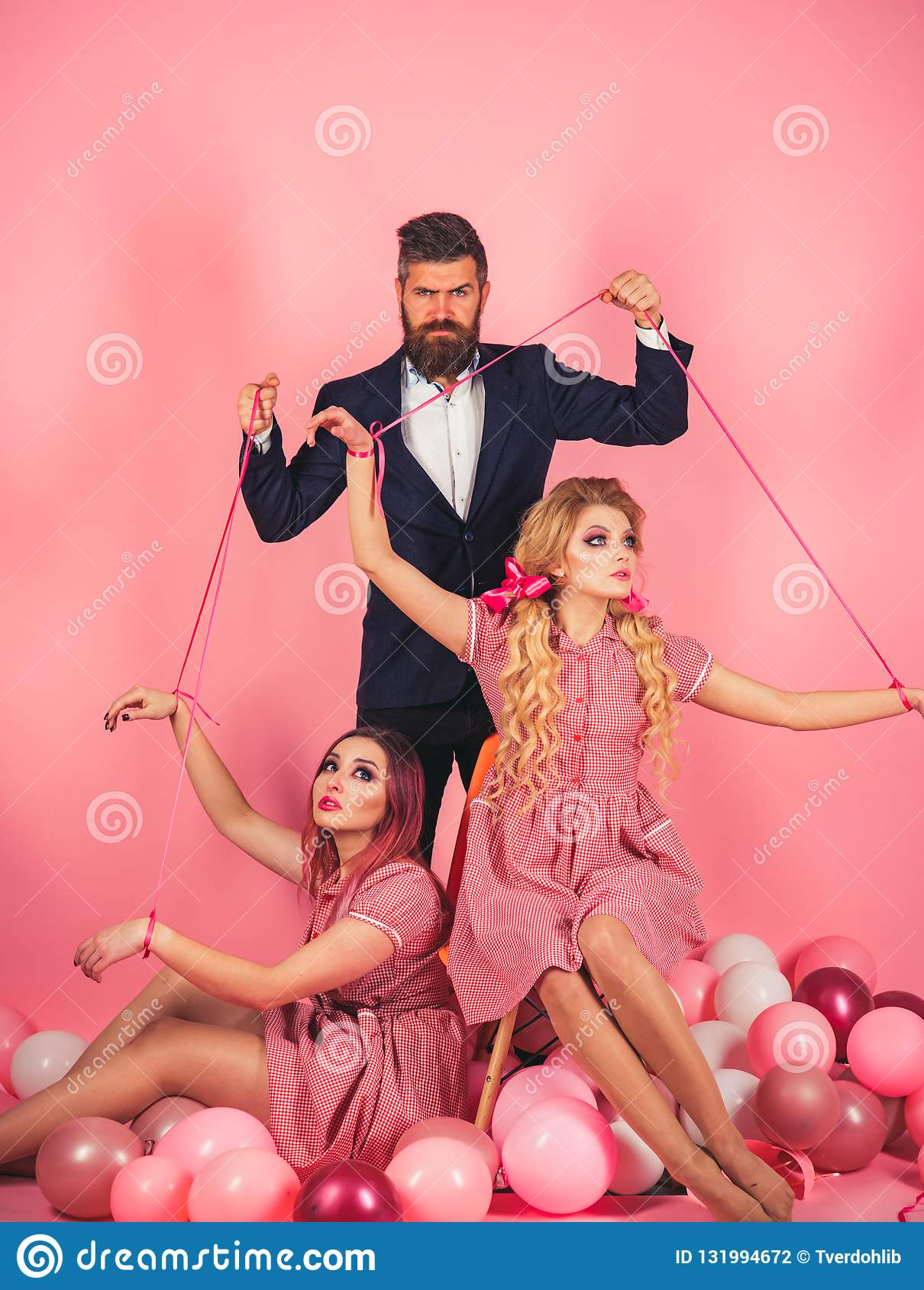 Crazy girls and man on pink. Halloween. Creative idea. Love triangle. retro girls and master in party balloons. vintage