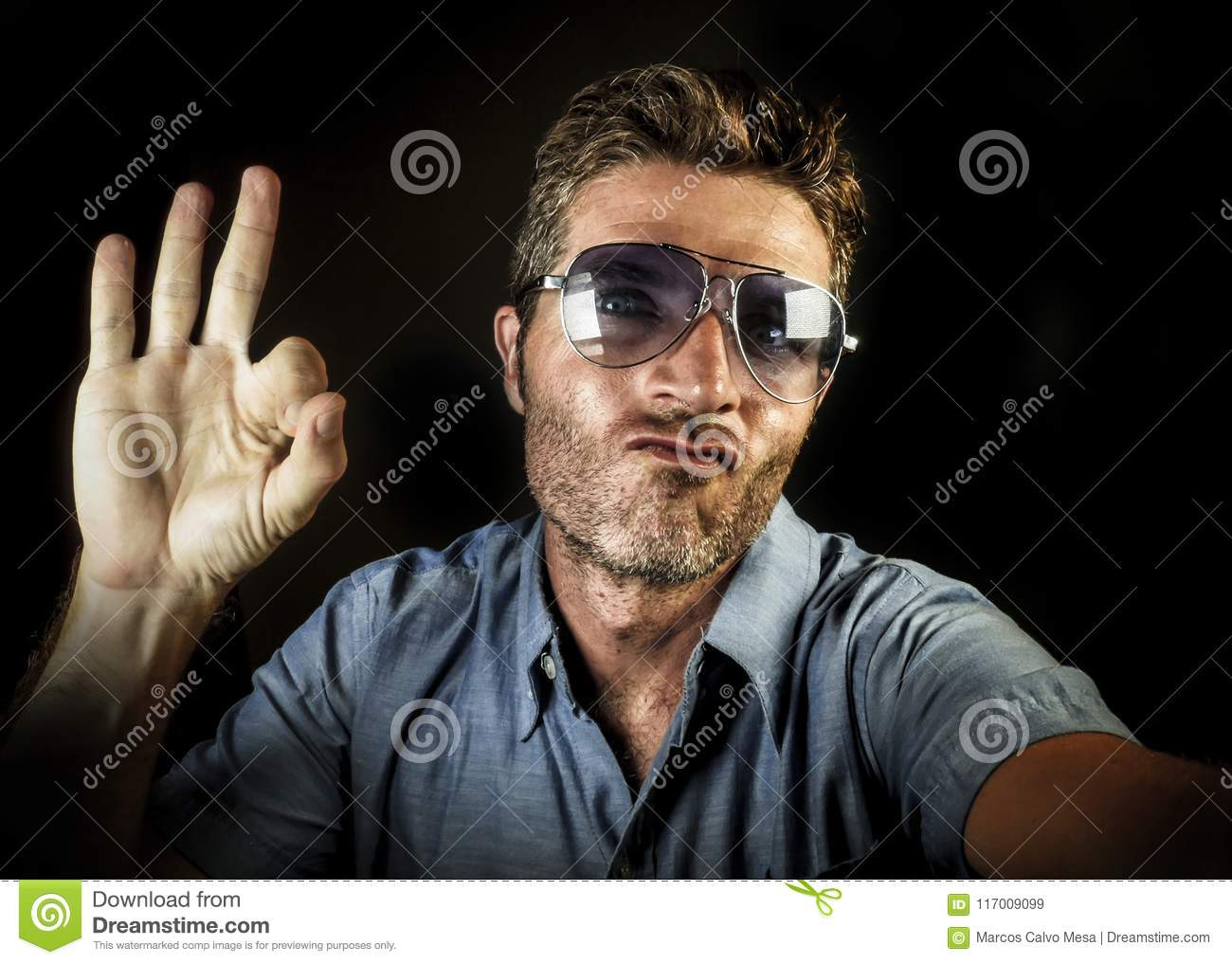 Crazy happy and funny guy with sunglasses and modern hipster look taking selfie self portrait picture with mobile phone camera smi