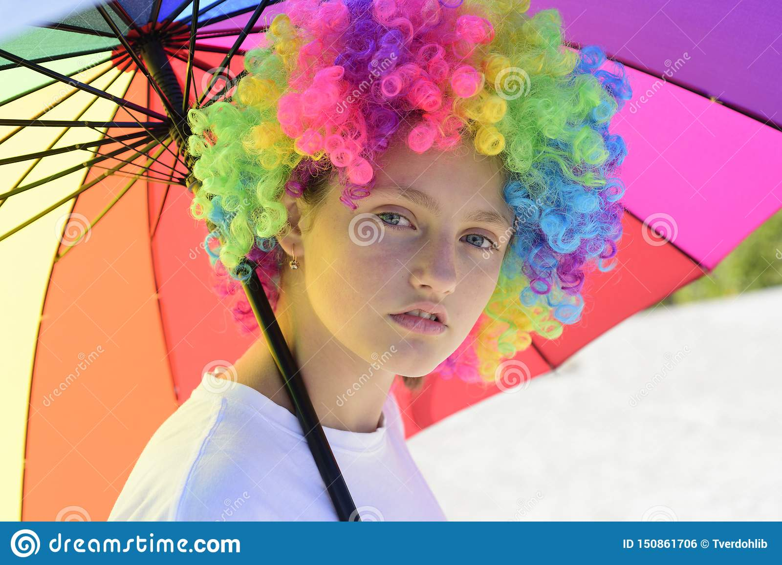 Crazy hipster girl. fashion girl with colorful hair wig and umbrella. kid in summer camp. happy youth party. autumn