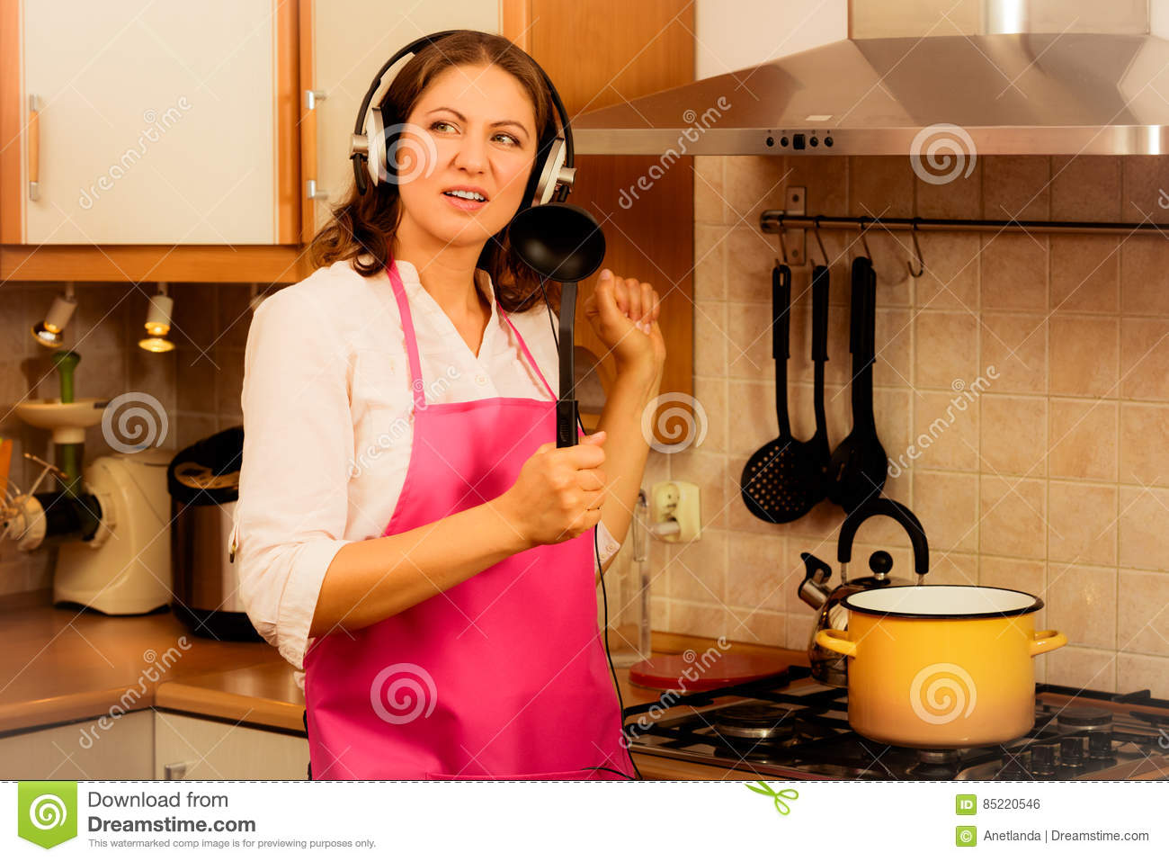 Modern beauty woman housewife cook chef wearing pink apron listening music on earphones singing and dancing in kitchen