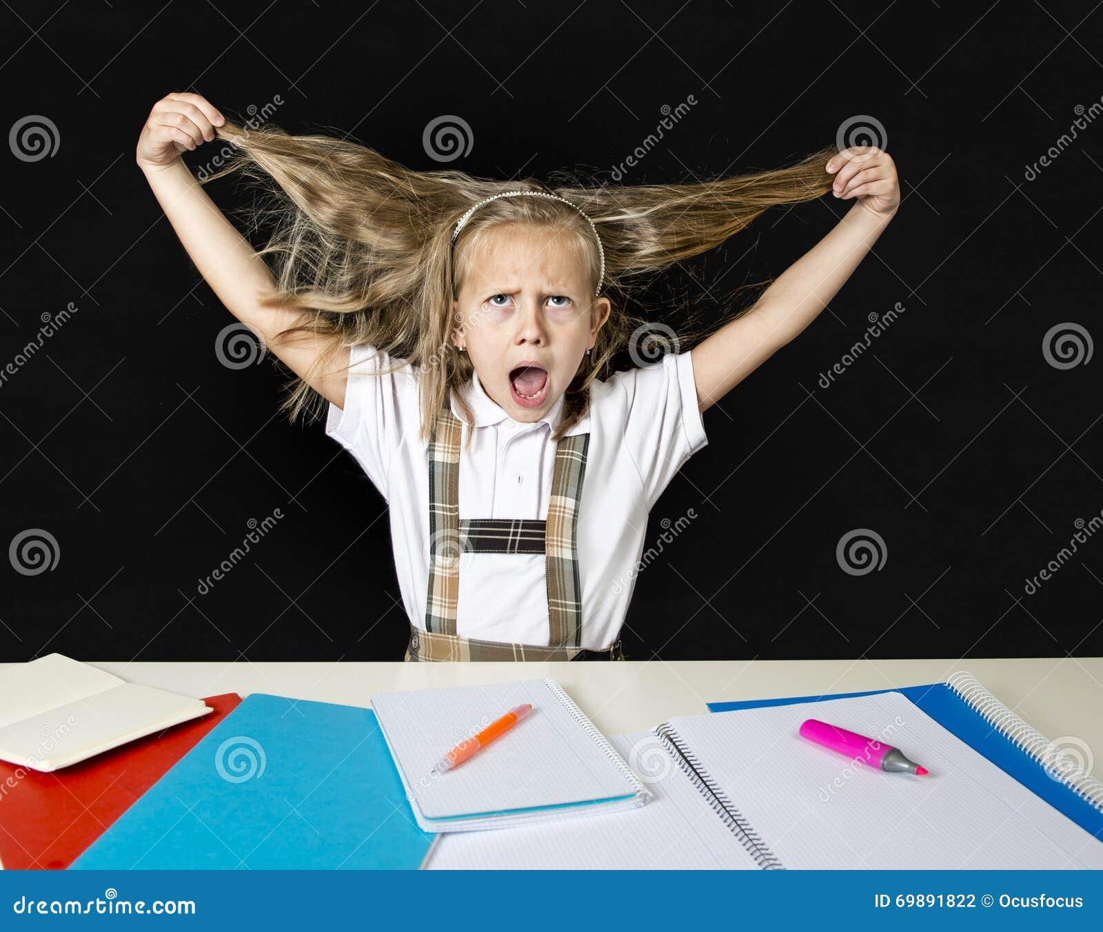 Crazy junior schoolgirl sitting on desk in stress working doing homework pulling her blond hair crazy