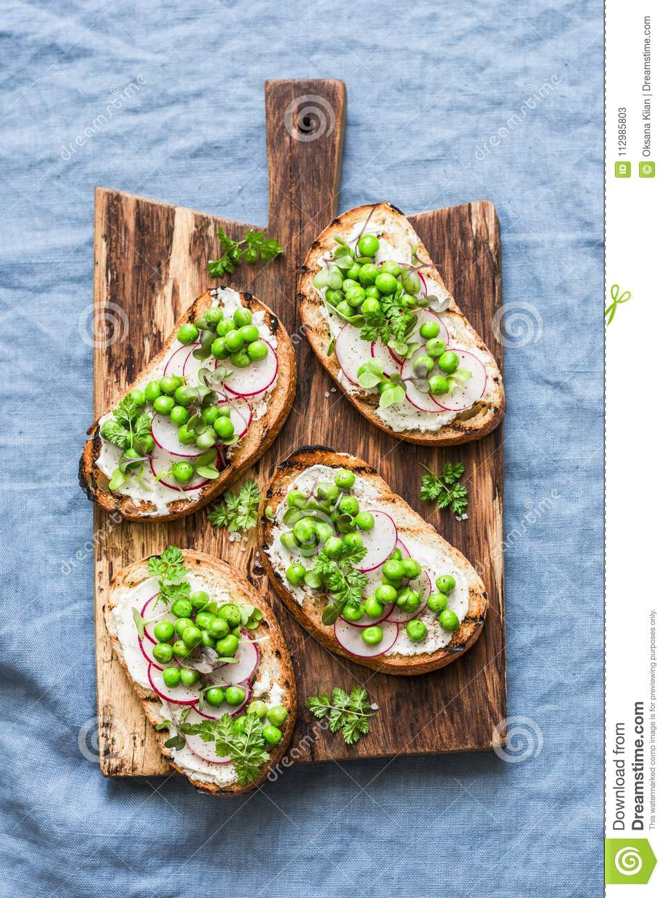 Cream cheese, green peas, radishes and micro greens spring sandwiches on a cutting board. Healthy eating, slimming, diet lifestyle