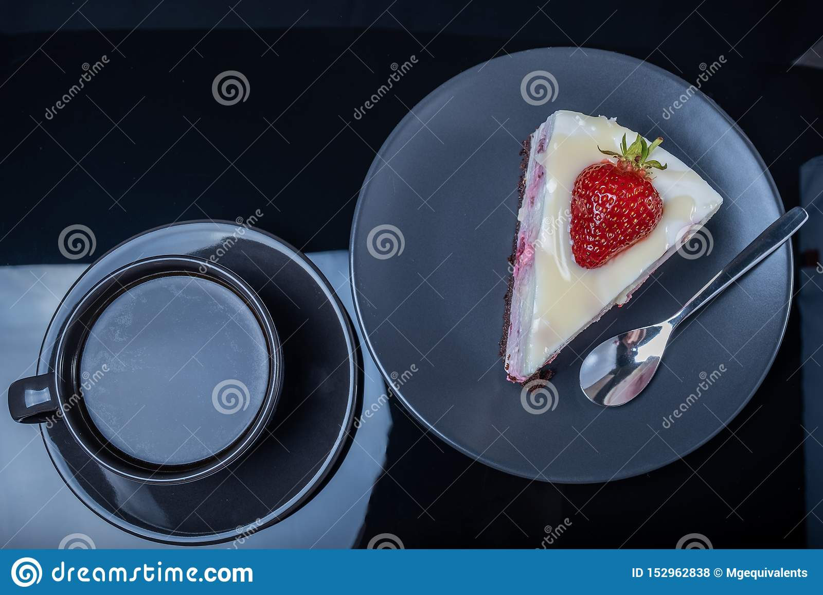 Cream fruit cake and a cup of black coffee on a black glass table