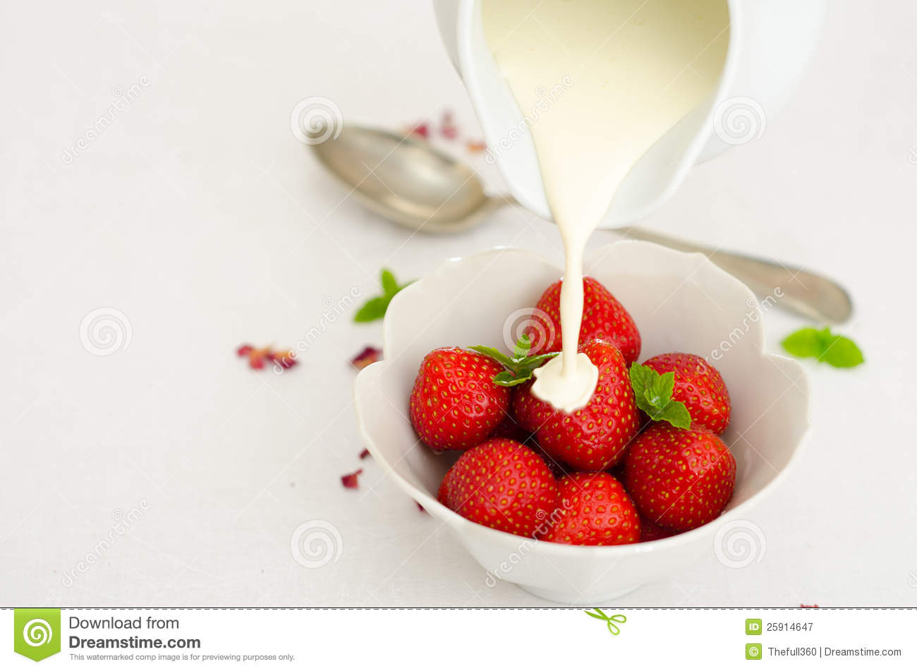 Cream Pouring From A Jug Over Fresh Strawberries Stock ...