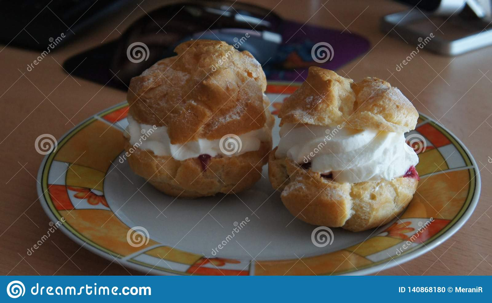 Cream puffs with cherries and sweet cream filling.