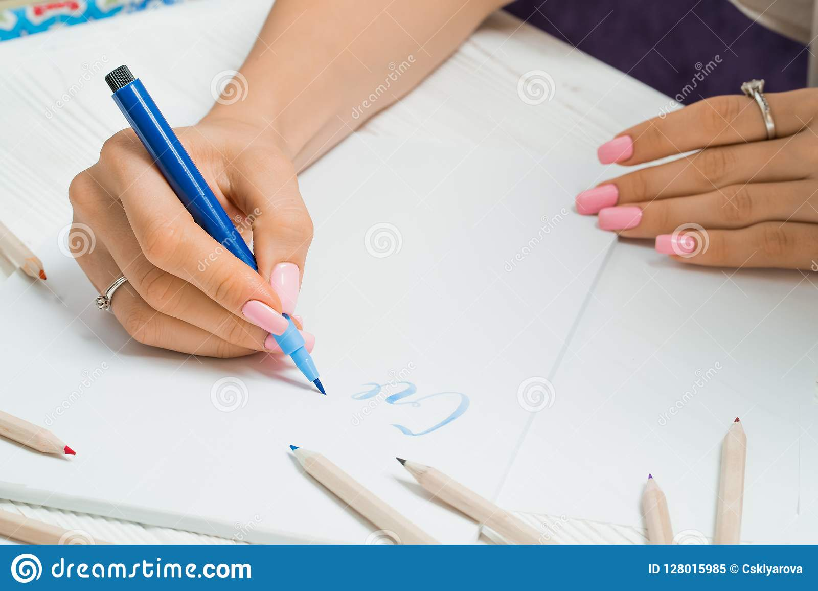 Create. Female hand writes beautiful blue letters on canvas in colorful pens frame. Calligraphy script. Art of writing