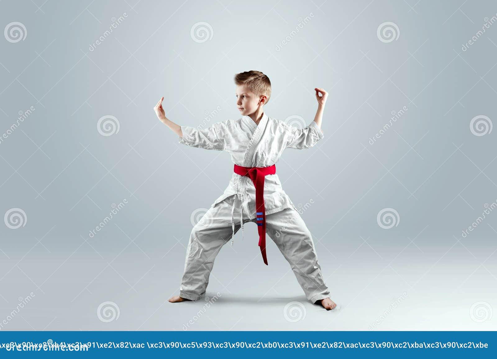 Creatieve achtergrond een kind in een witte kimono in een het vechten houding, op een lichte achtergrond het concept vechtsporten