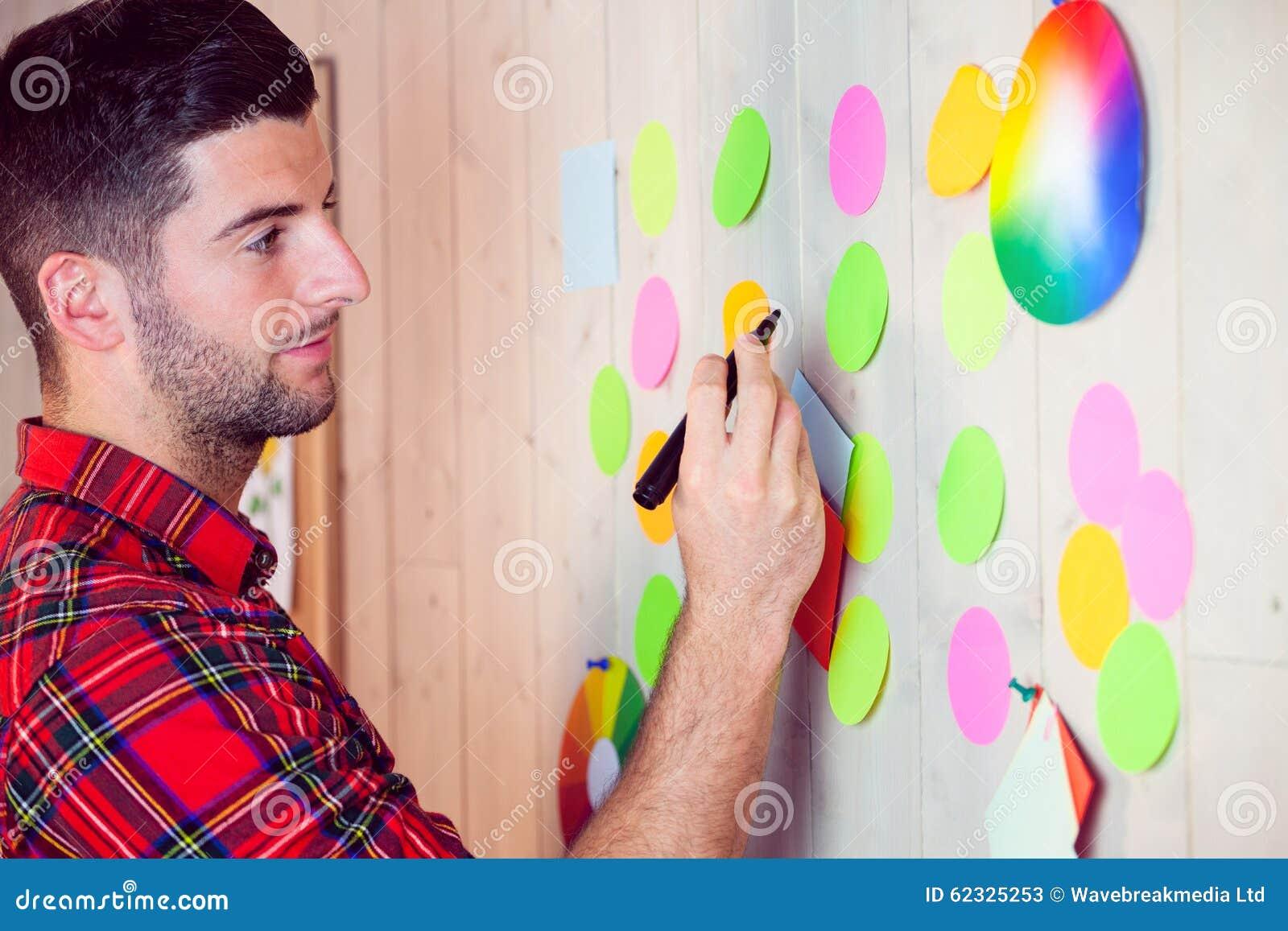 Creatieve arbeider die muur voor uitwisseling van ideeën gebruiken ...