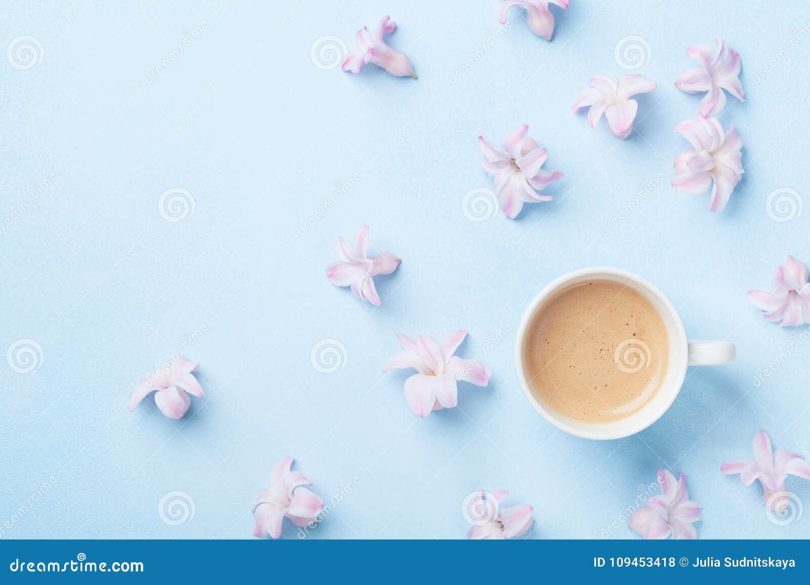 Creatieve samenstelling met ochtendkoffie en roze bloemen op blauwe pastelkleur hoogste mening als achtergrond vlak leg stijl