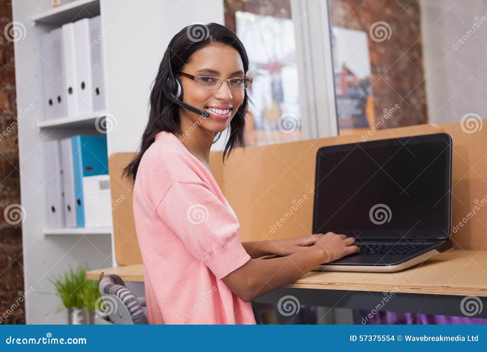 Creatieve vrouw met hoofdtelefoon die computer met behulp van bij bureau