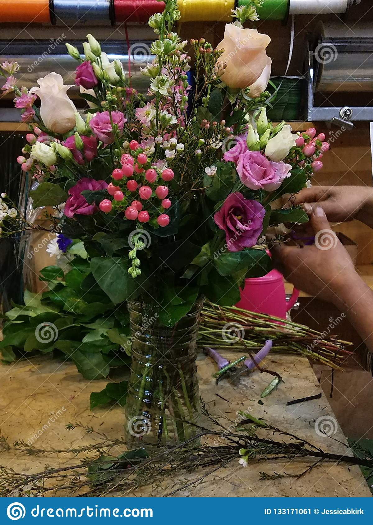 Creating a floral bouquet with mixed pink colors at the flower shop. Florist hands working diverse ethnicity.