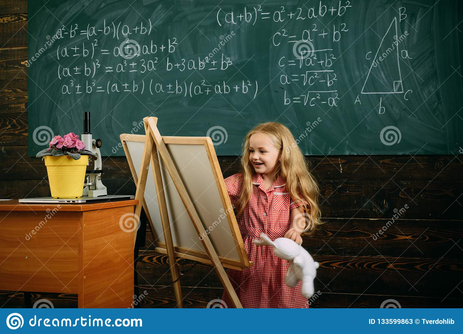 Creative artist painting on studio easel. Little artist girl creating picture in class