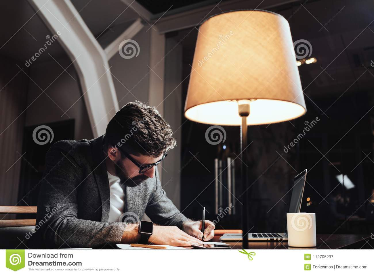 Creative businessman working with paper documents and contemporary laptop at late evening in loft office. Bearded young man sits b