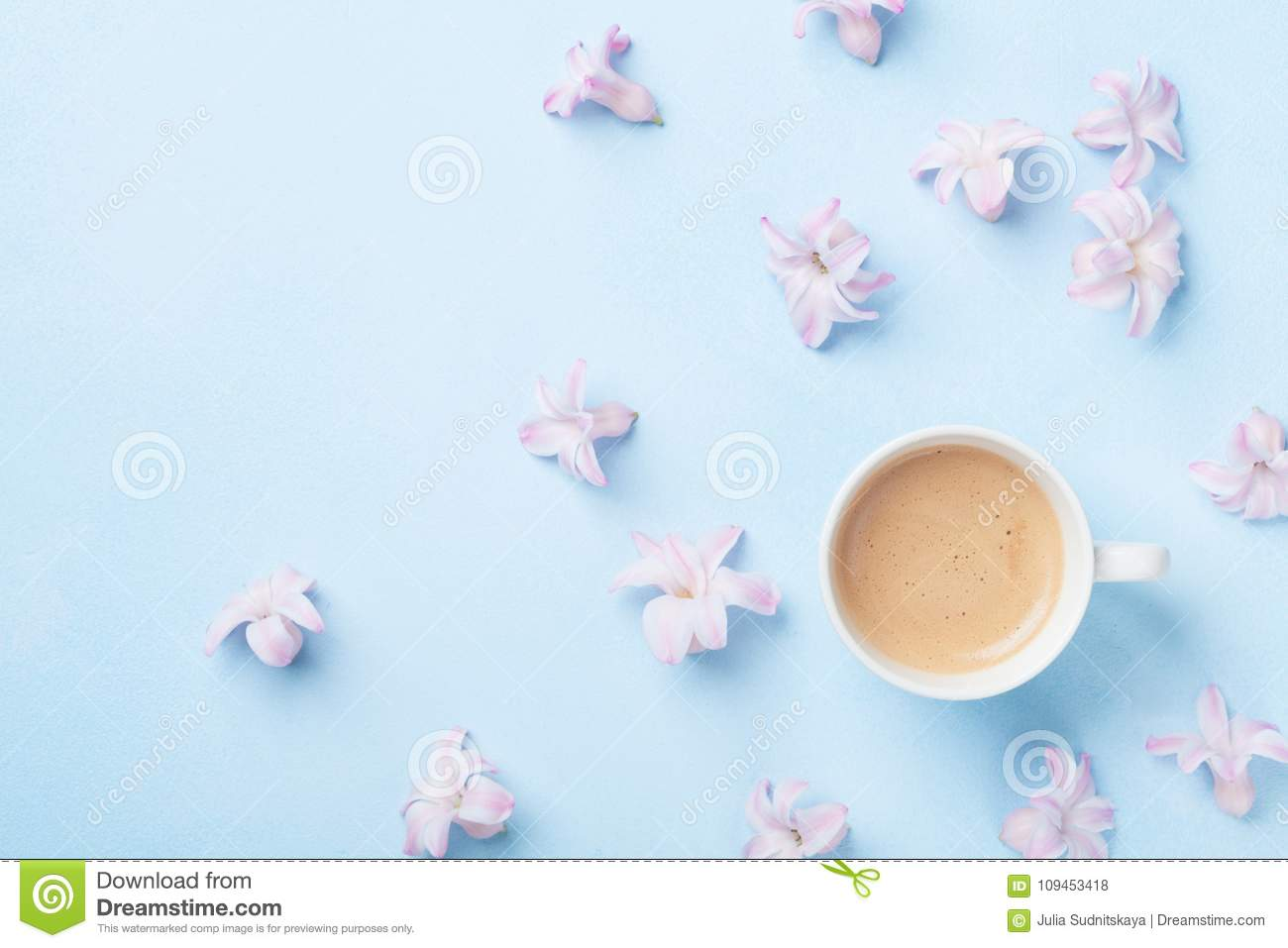 Creative composition with morning coffee and pink flowers on blue pastel background top view. Flat lay style.
