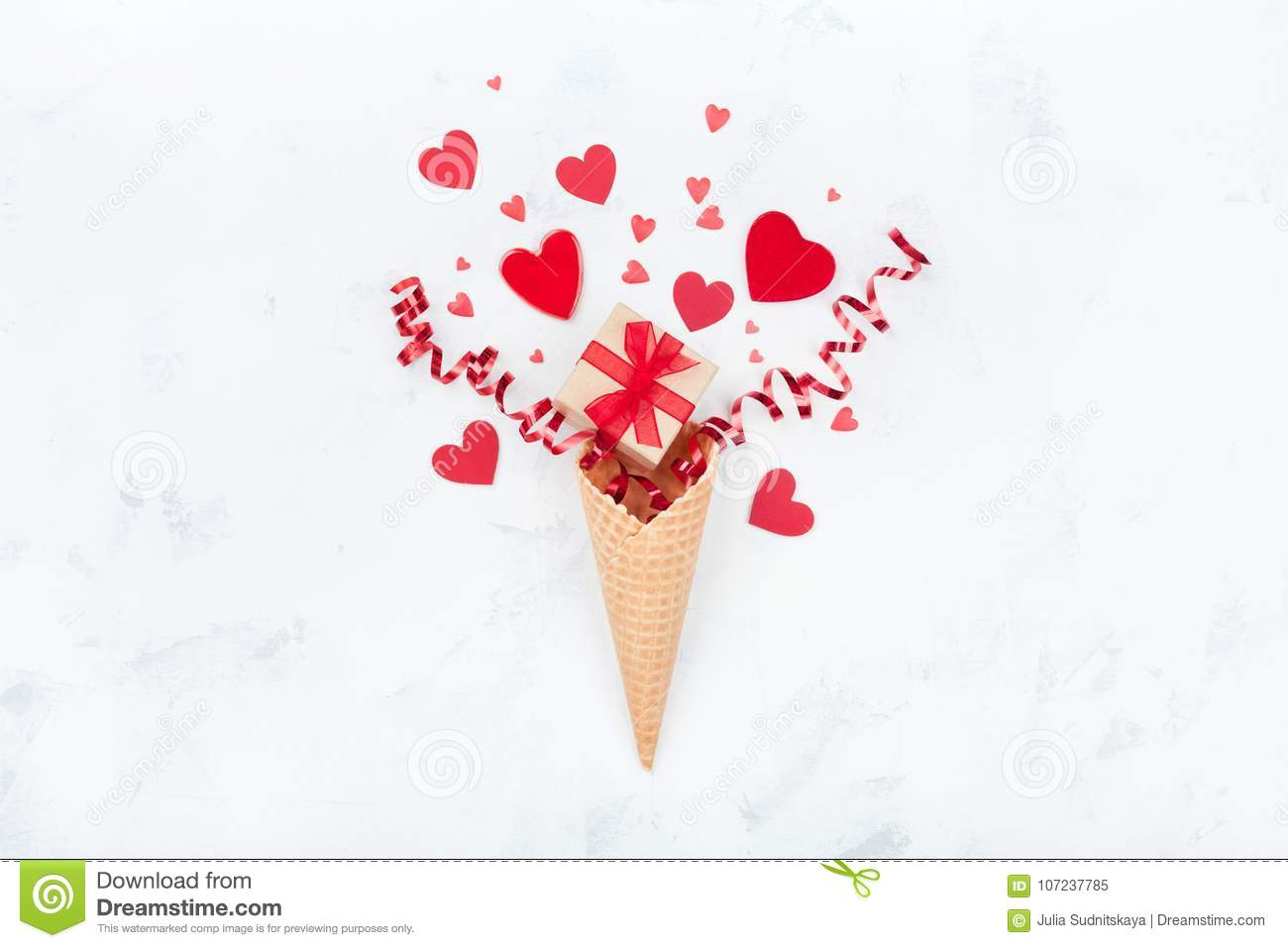 Creative composition for Valentines day with waffle cone, gift or present box and hearts on white background top view. Flat lay.