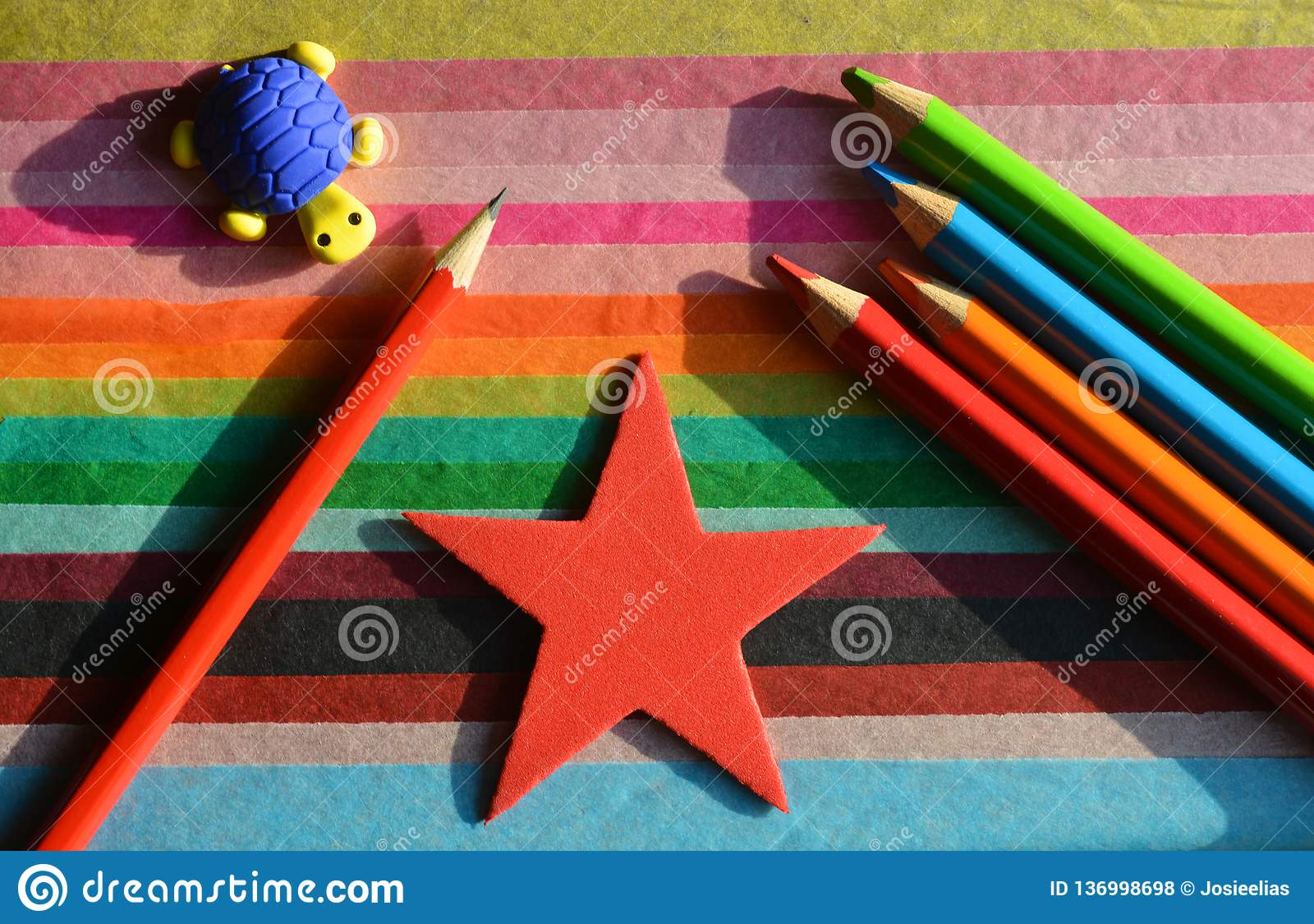 Creative Concept, Back to School. Pencil and crayons on a colourful background
