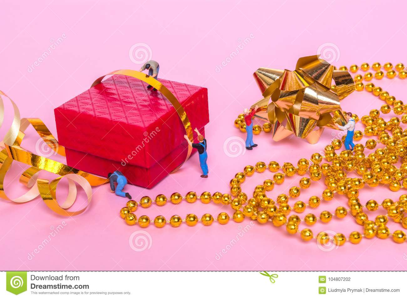Creative Concept With Miniature People And A Gift Box On A Pink