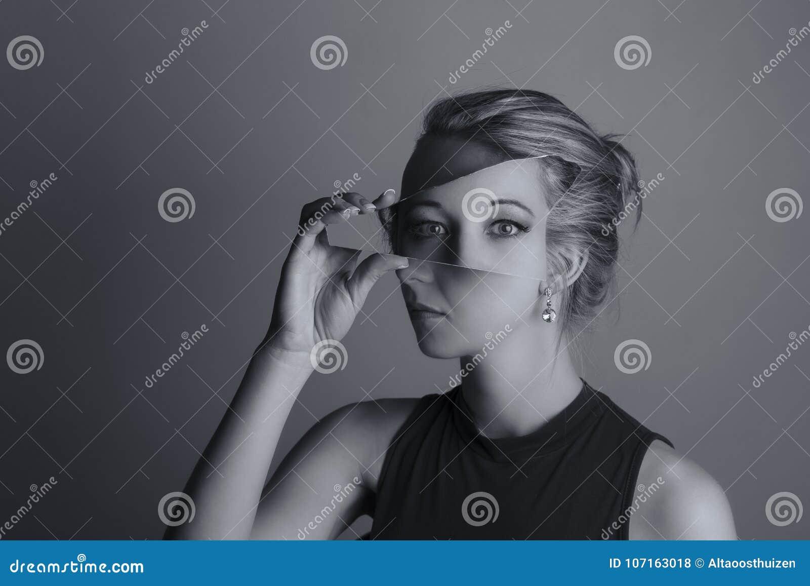 Creative conversion of woman holding a shard of broken mirror